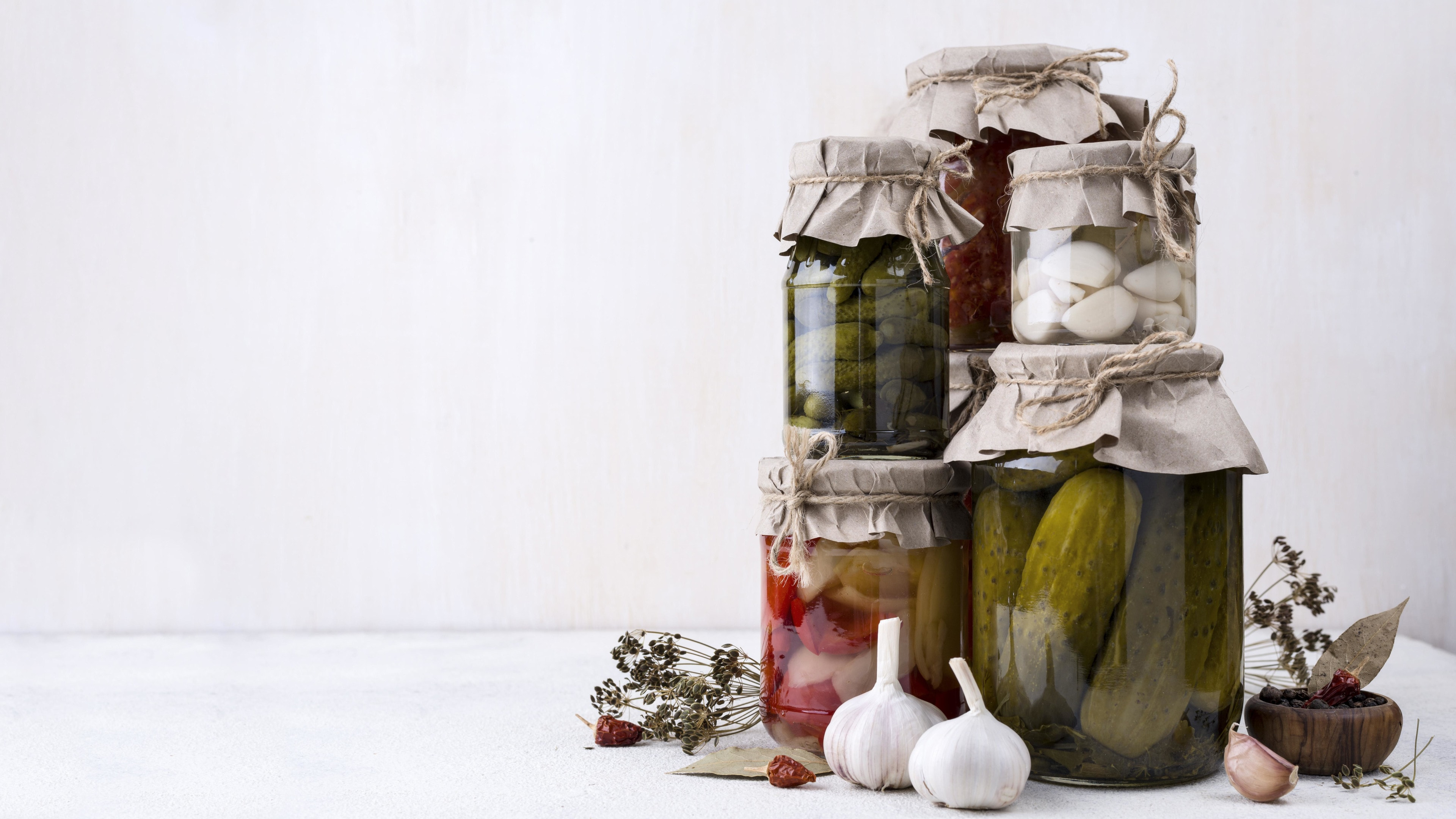 Jars assortment with picked vegetables on white table