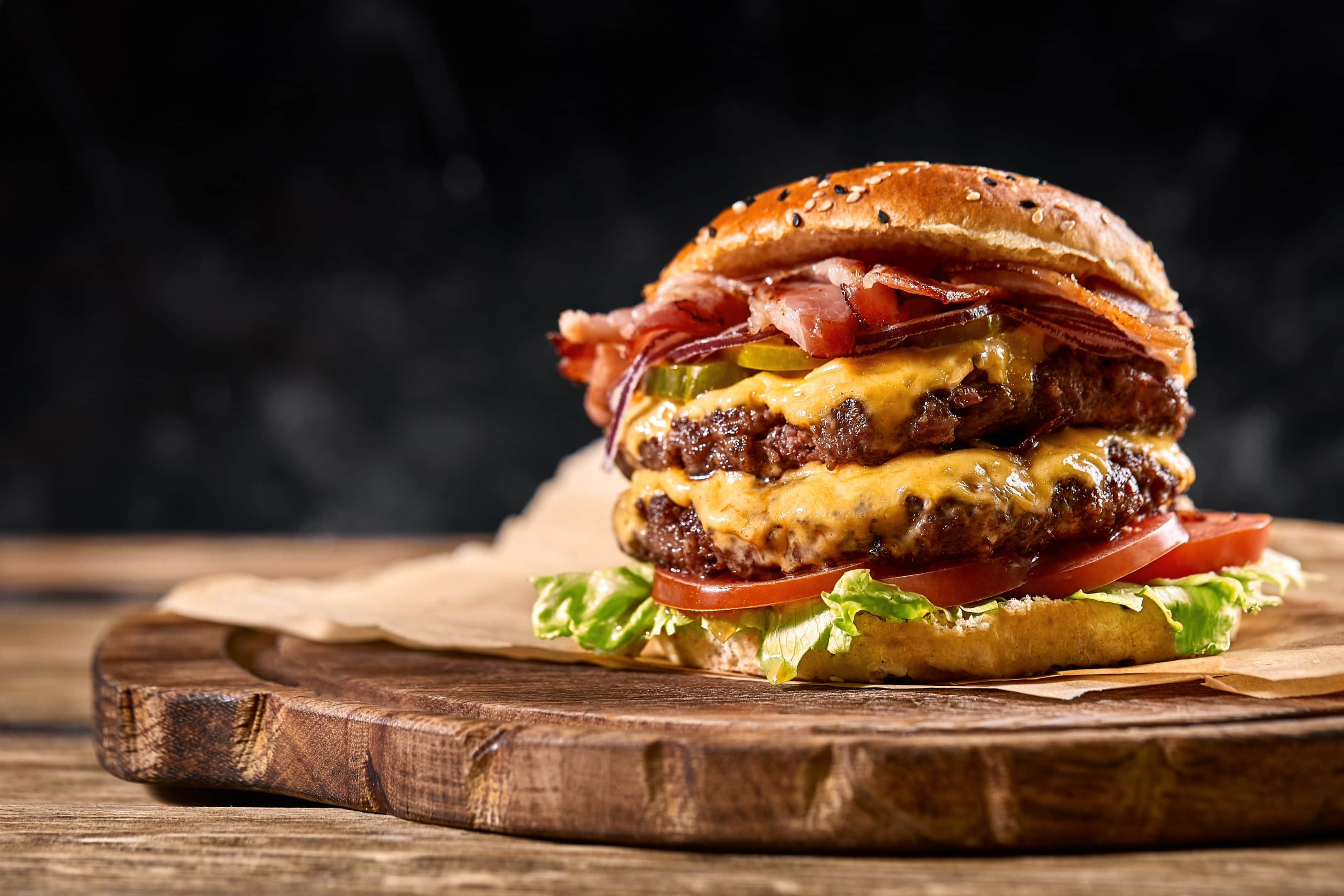 Juicy american burger cheeseburger with two beef patties and sauce on wooden board