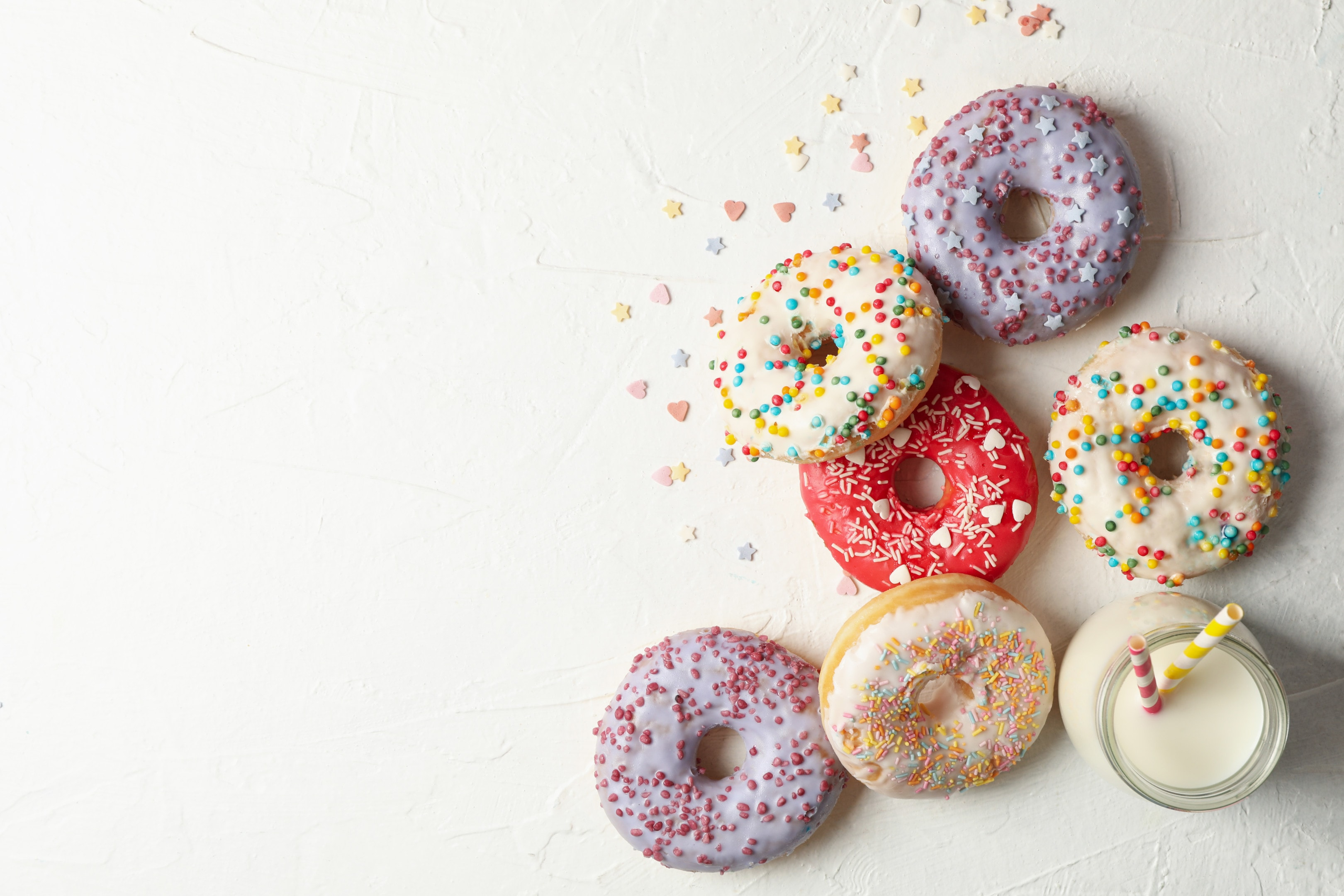 Milk and tasty donuts on white table