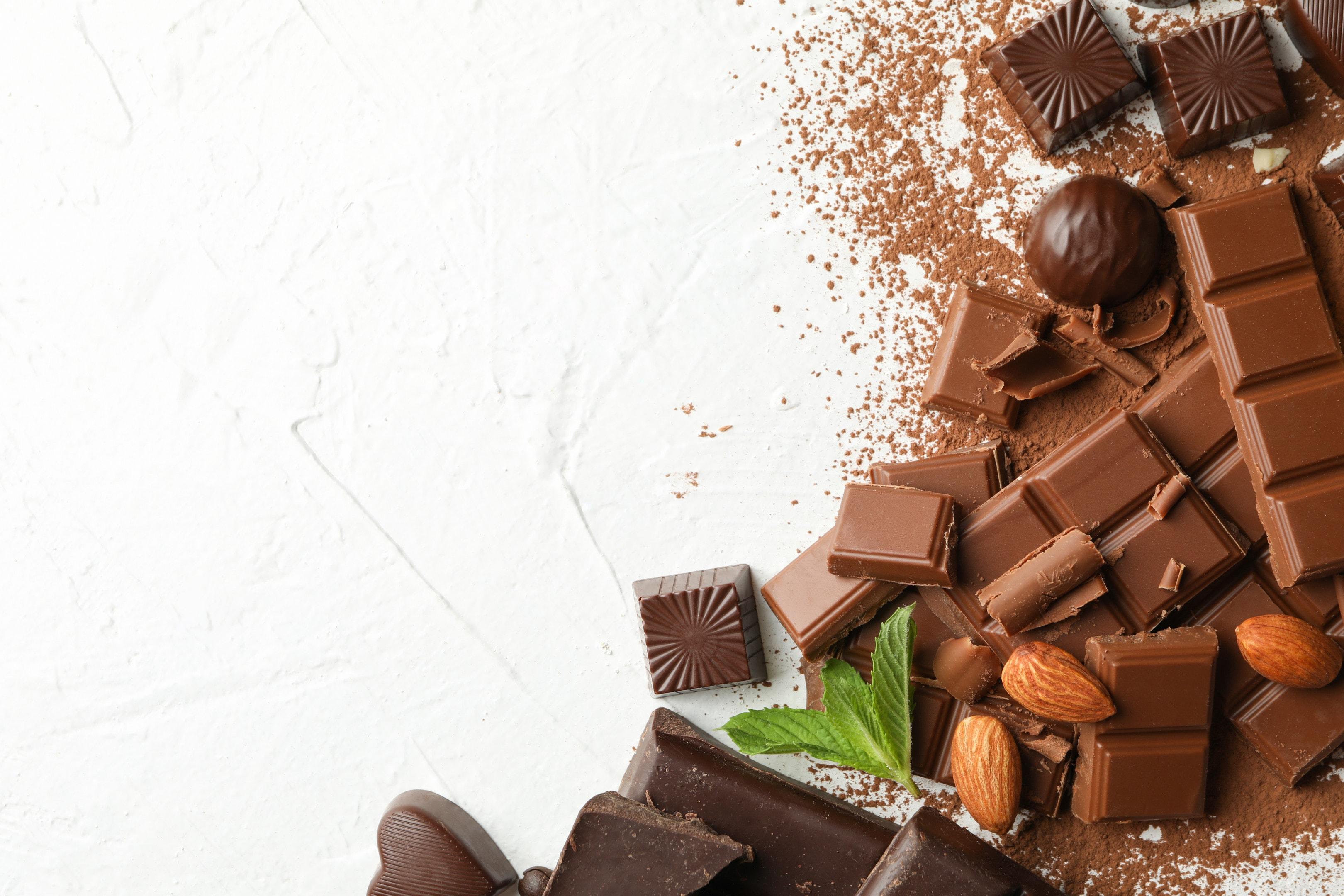 Milk chocolate and dark chocolate with almonds on white background