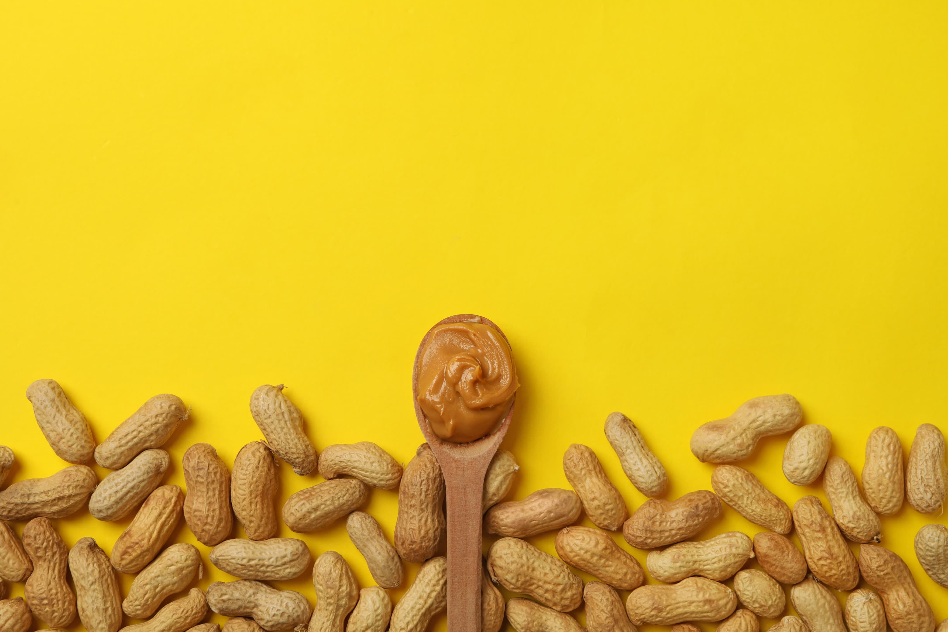 Peanut and spoon with peanut butter on yellow table