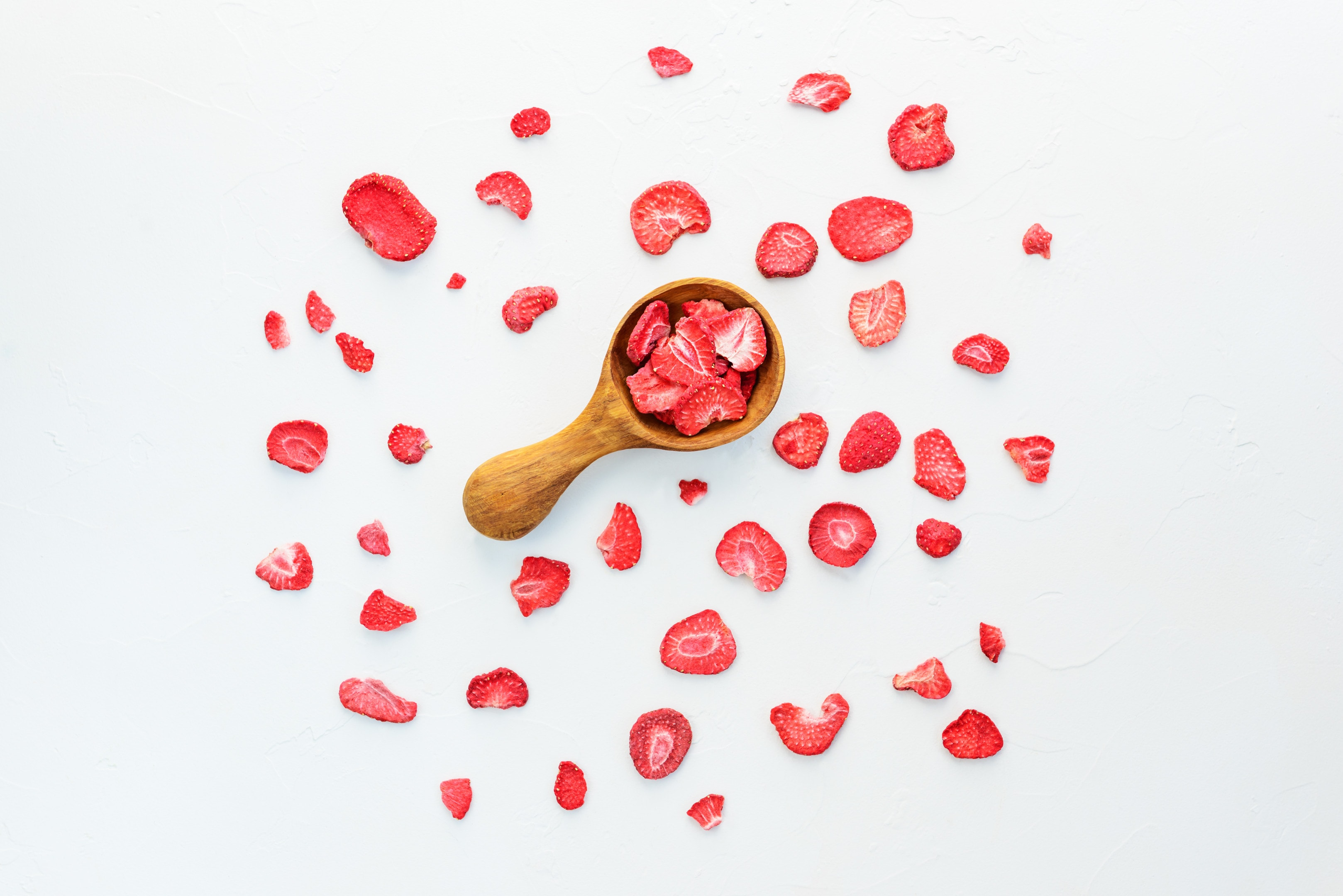 Pieces of dehydrated strawberries with wooden spoon on white background