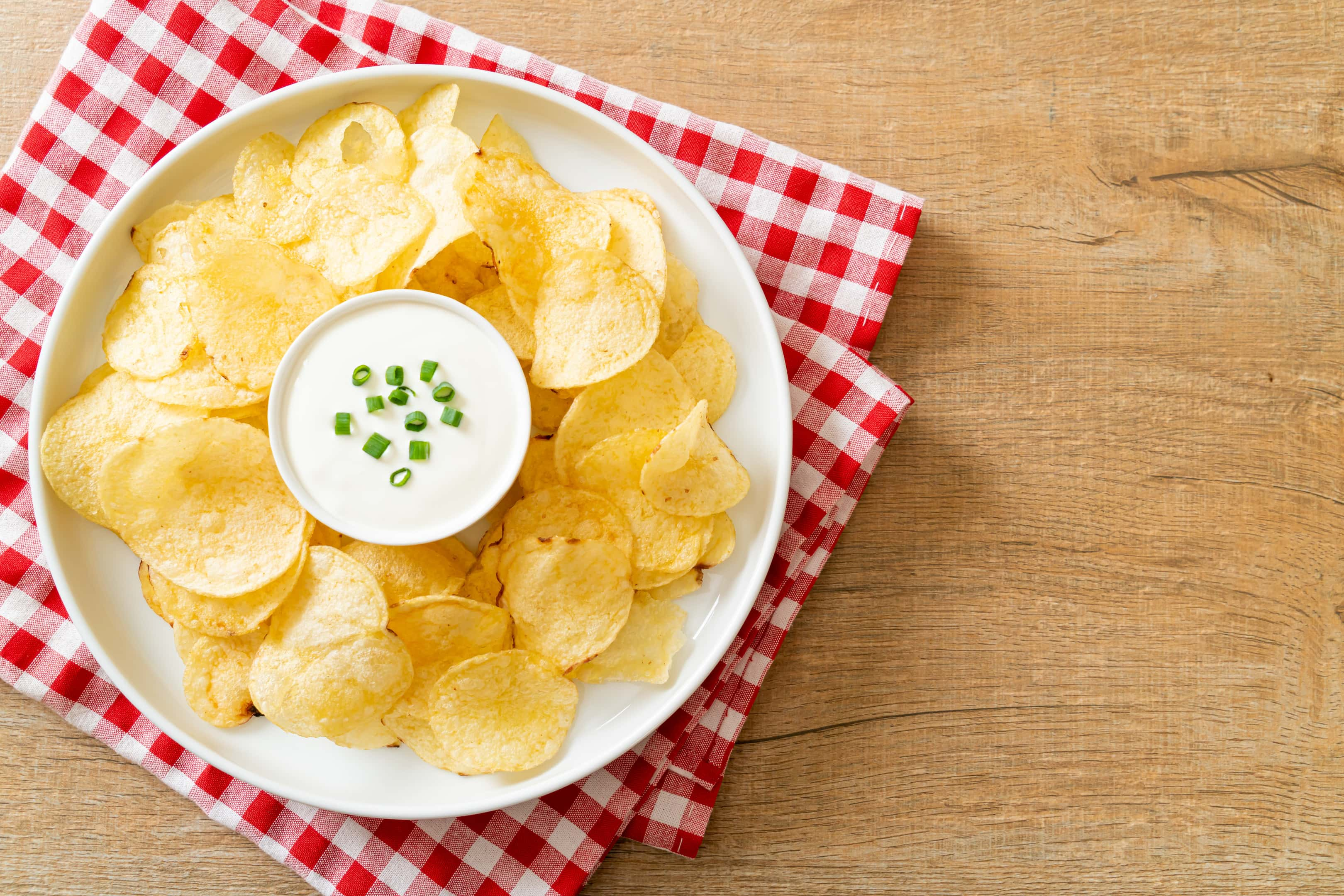 Potato chips with sour cream dipping sauce on a plate