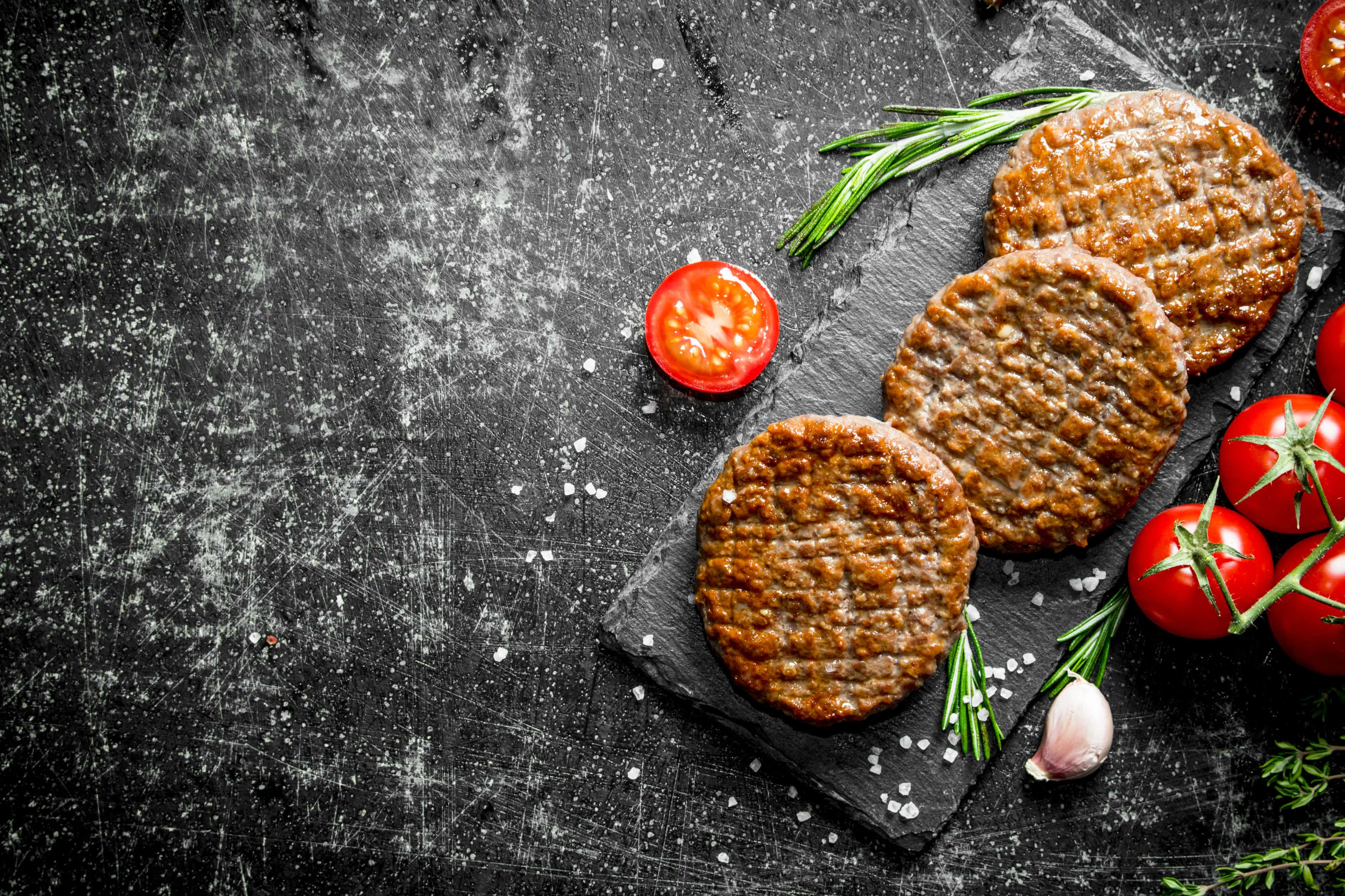 Processed hamburgers with tomatoes on black rustic stone board