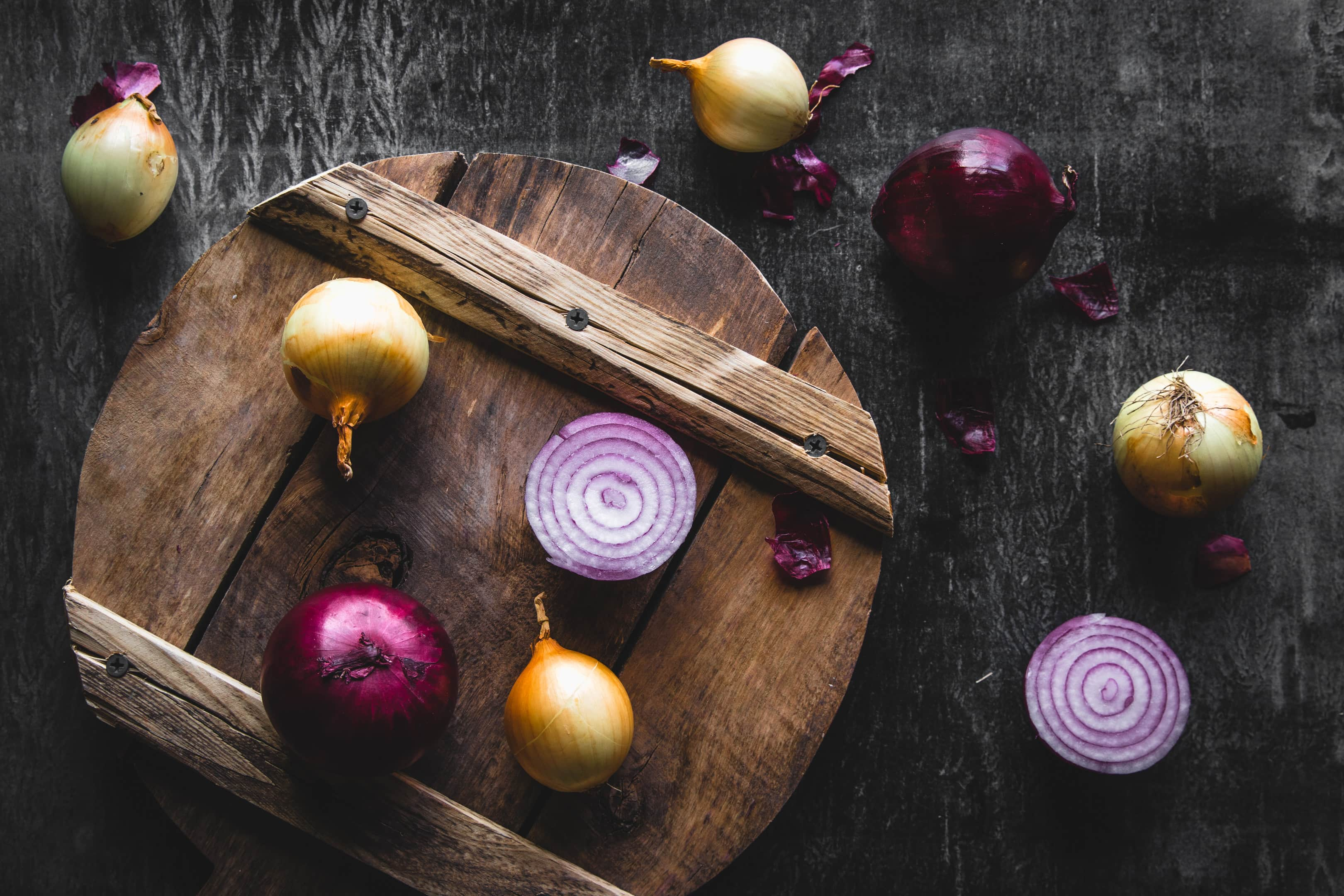Red onion slices and yellow onions on wooden board