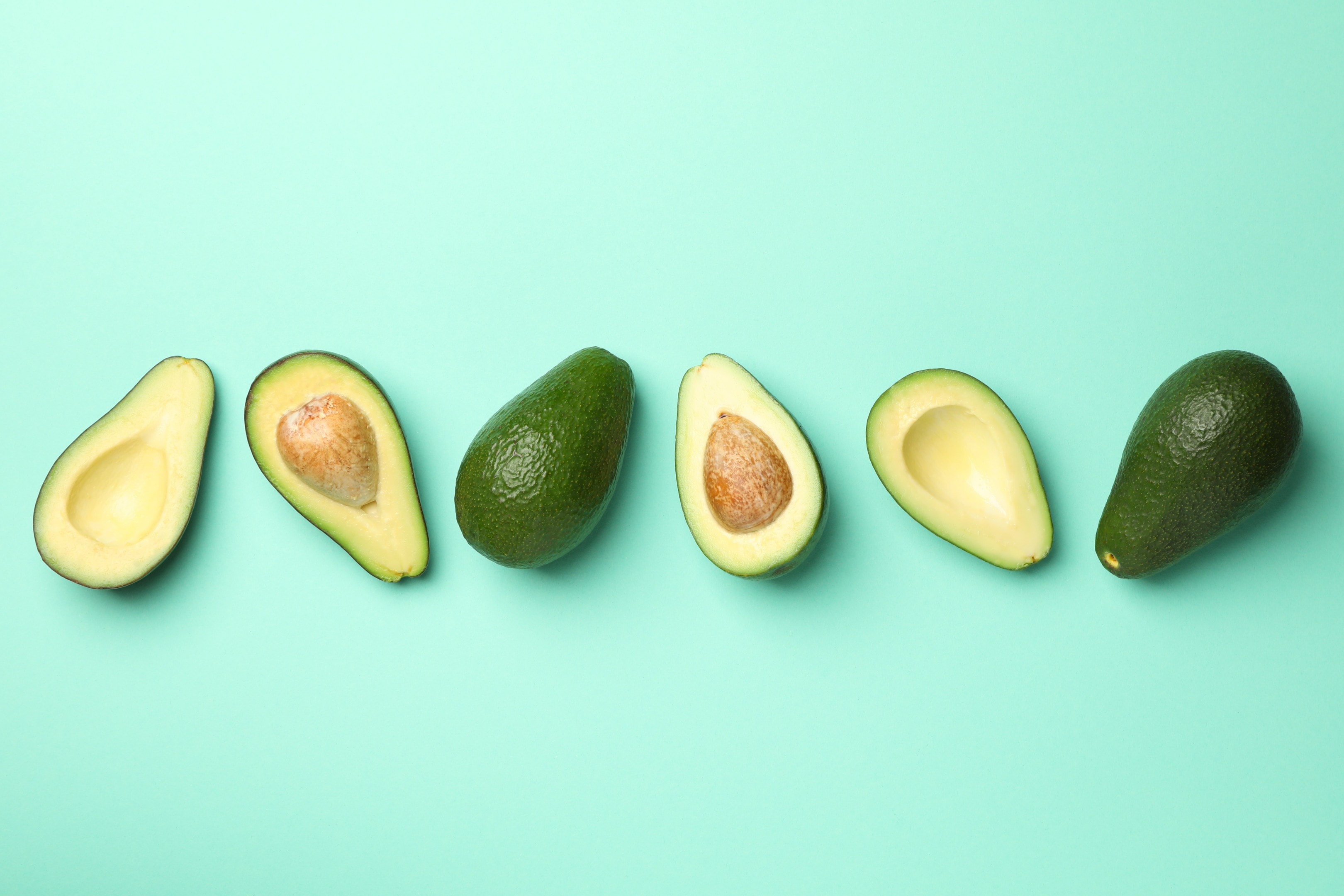 Ripe fresh avocado on mint background