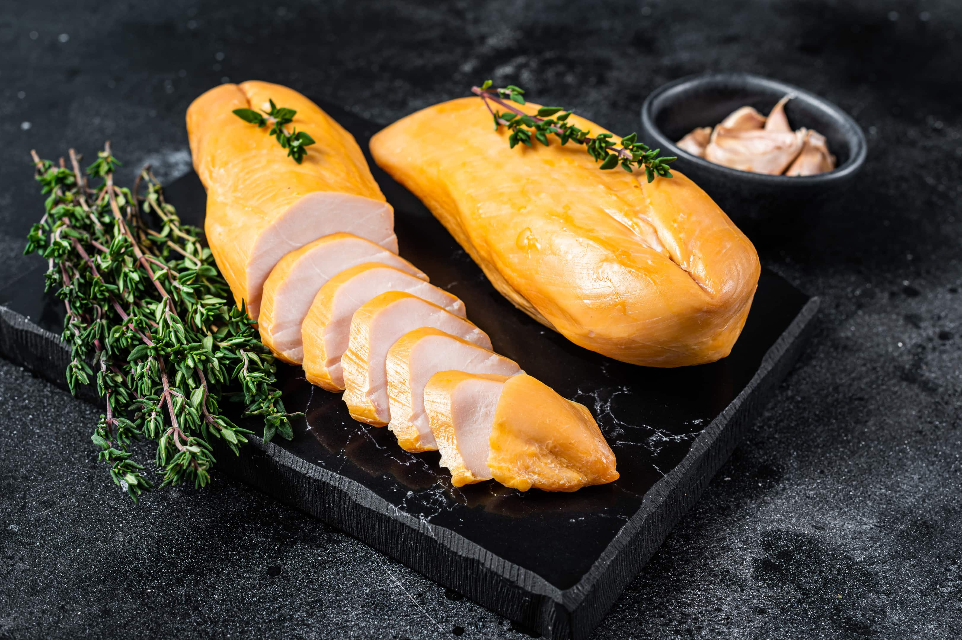 Smoked cut of chicken breast fillet on black table