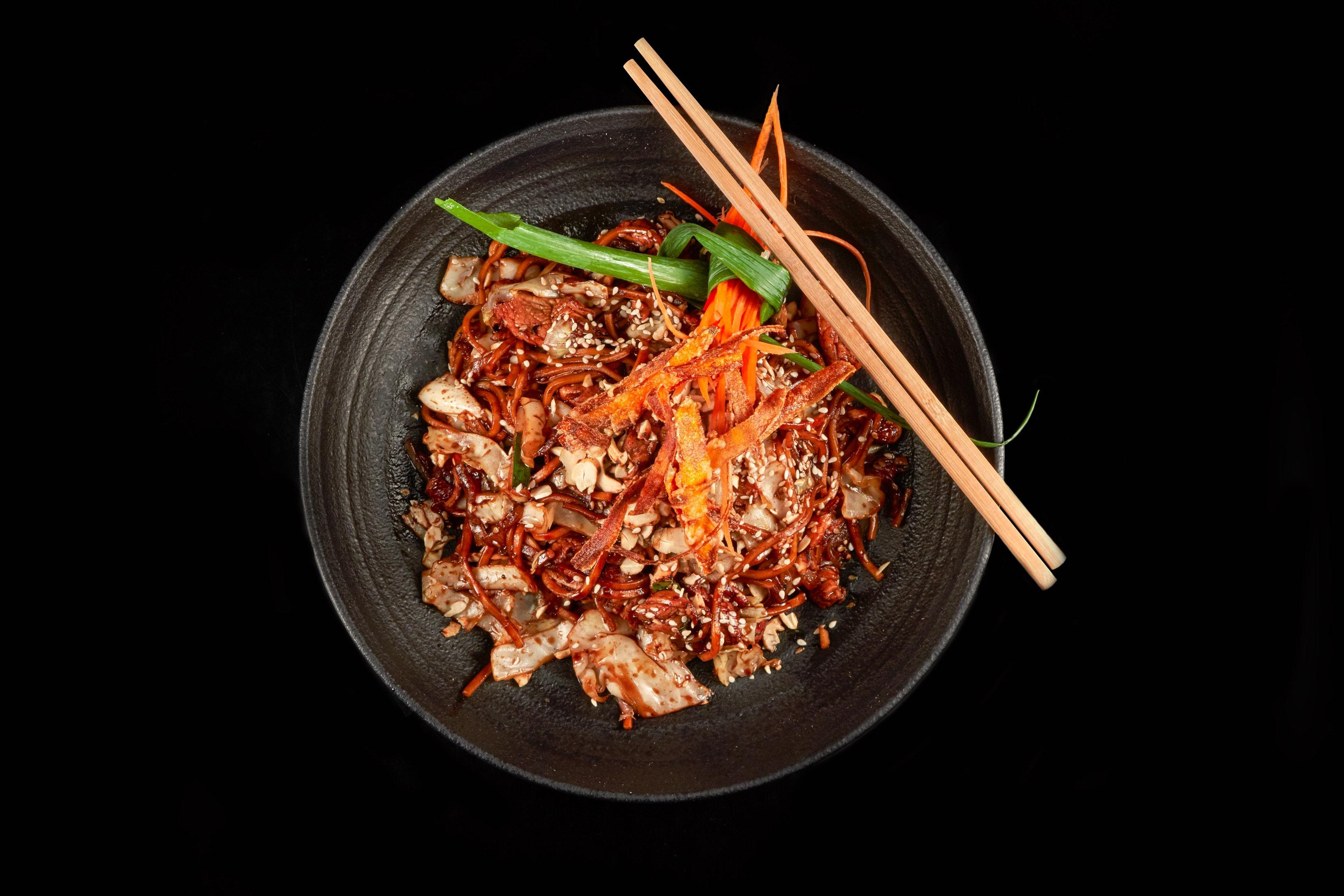 Stir-fry noodles seasoned with rice vinegar in black bowl