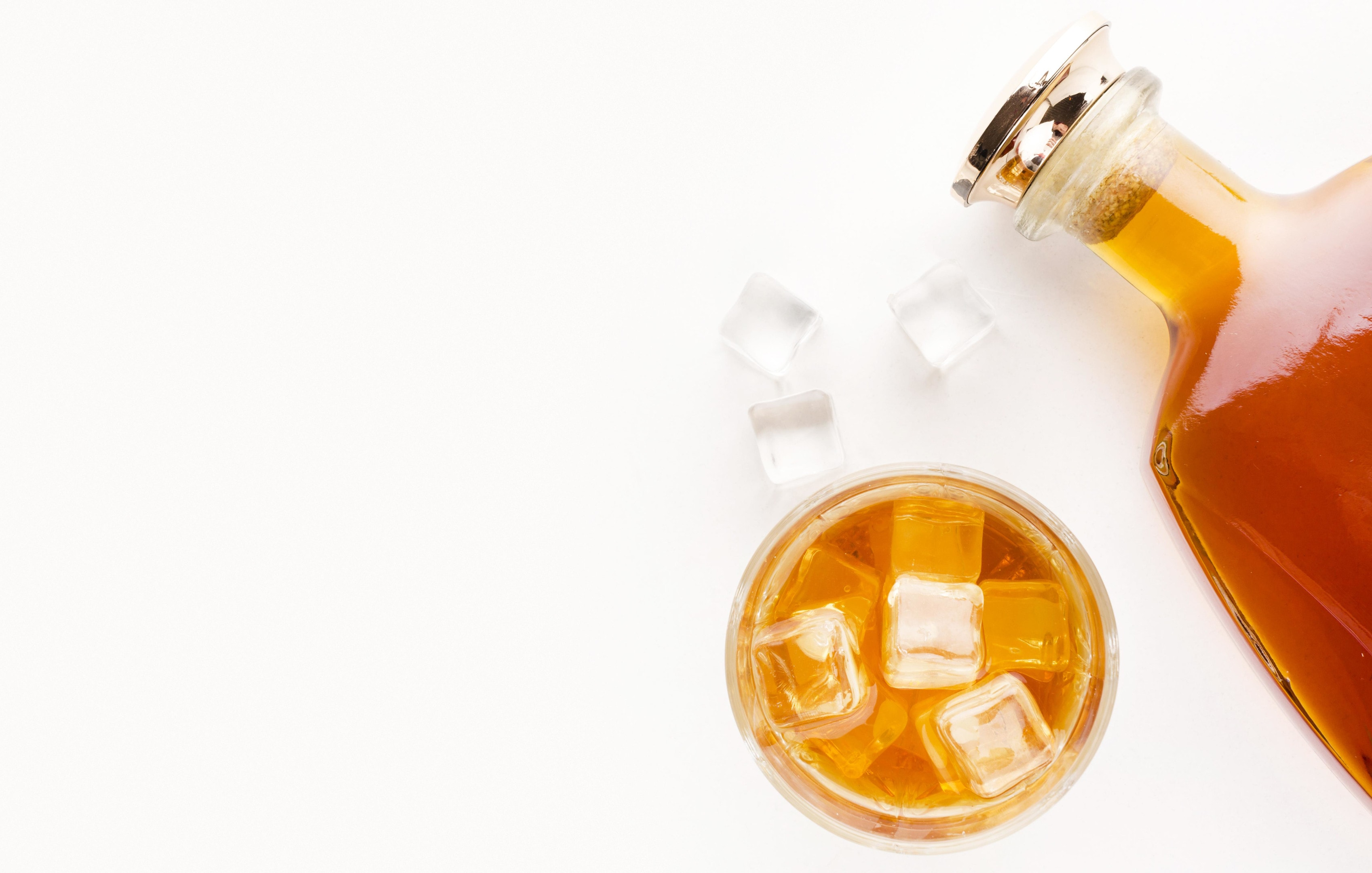 Whiskey bottle with glass on white background