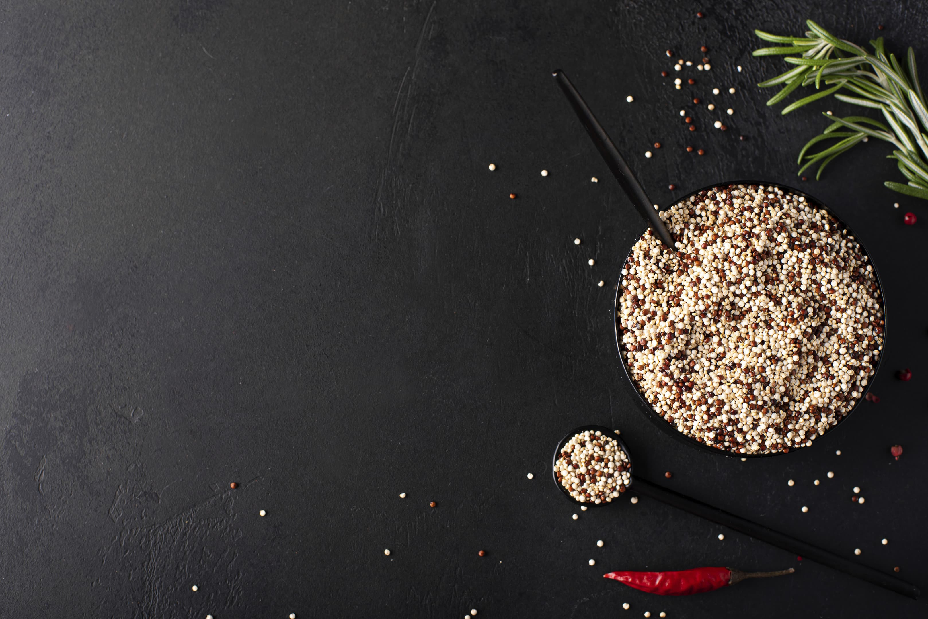 White and red quinoa grits with spices in black bowl