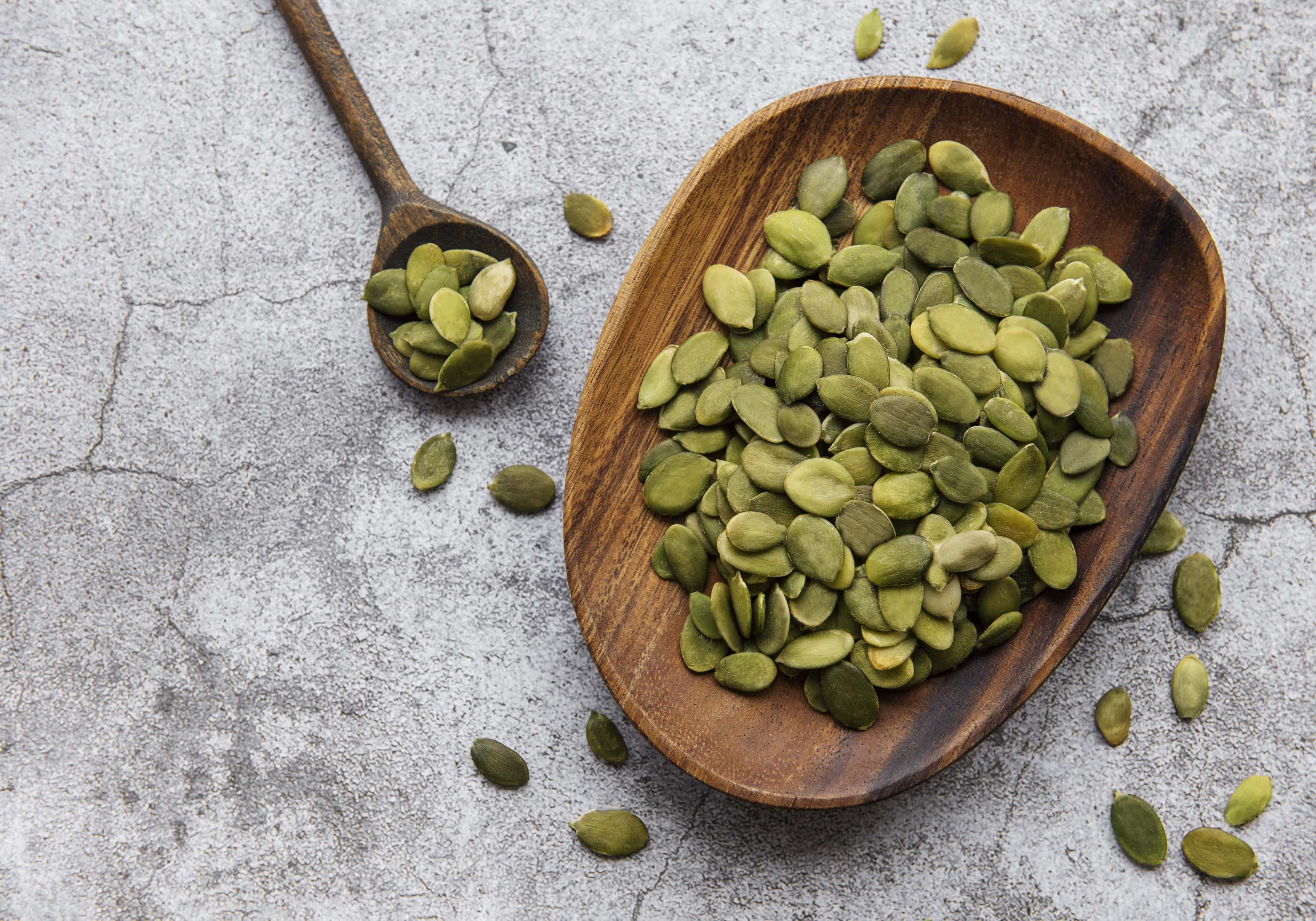 Wooden plate with pumpkin seeds on a gray concrete table