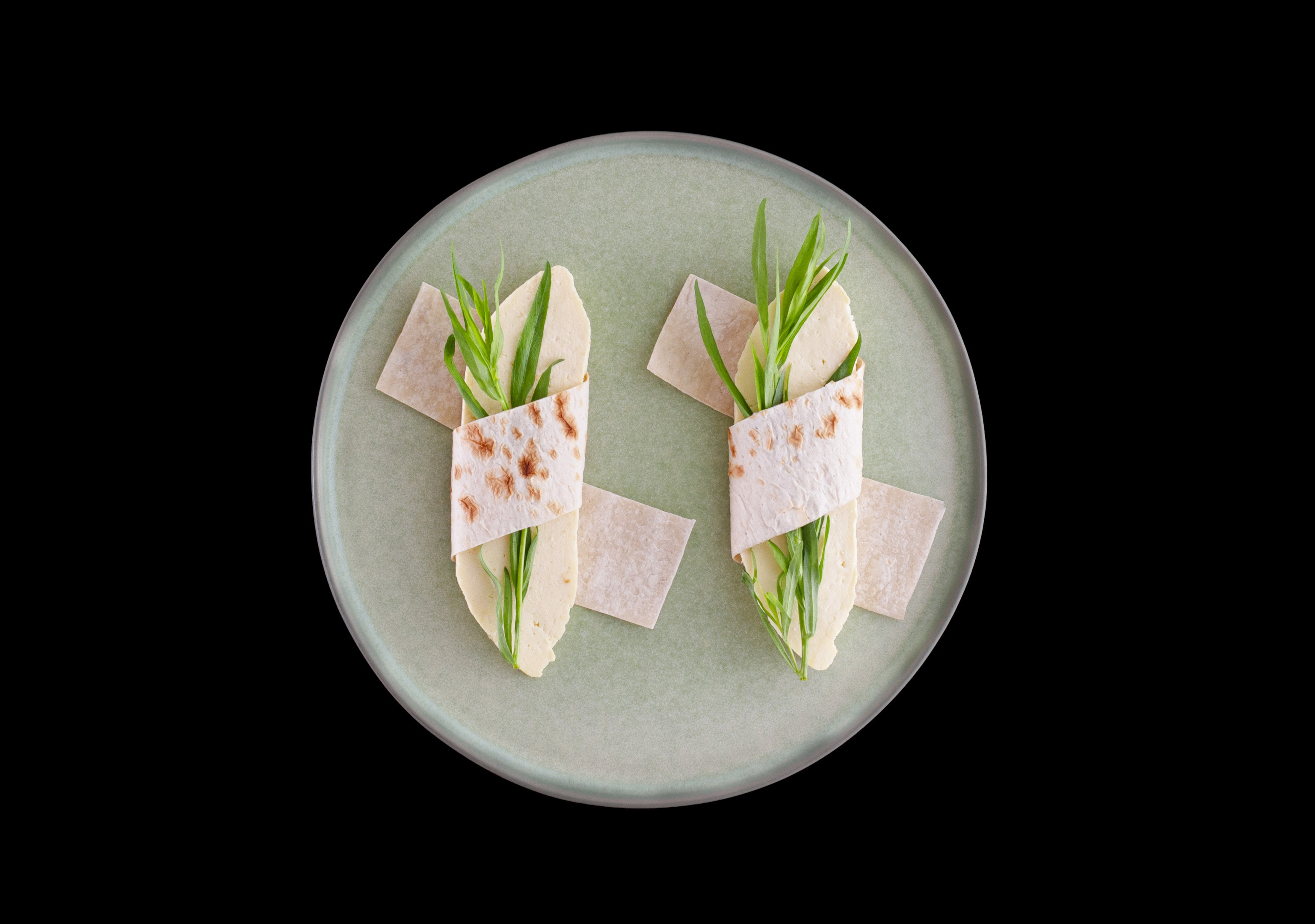 Wrapped pita bread with homemade cheese and semi-dry tarragon leaves on round plate