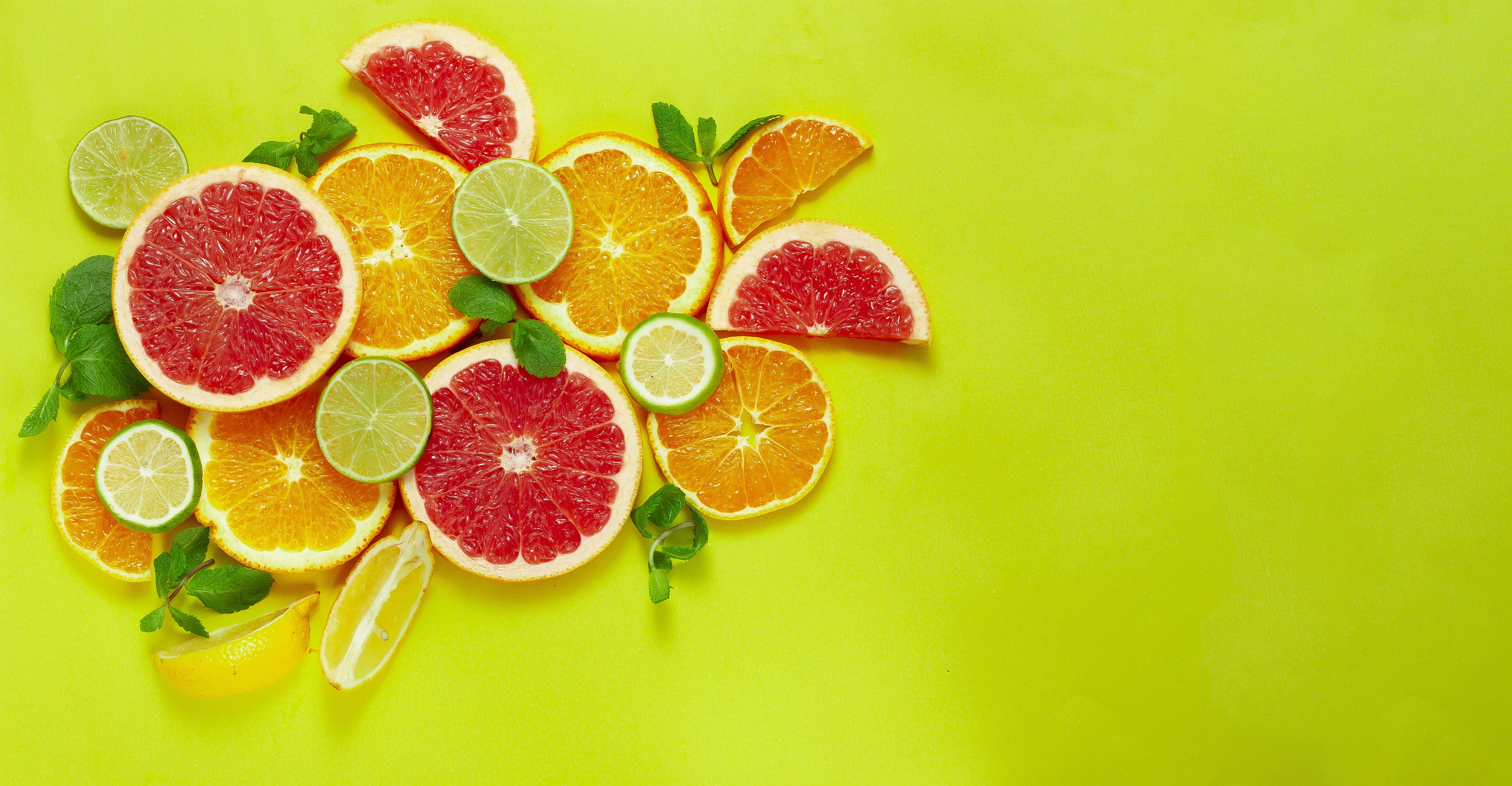 Assortment of citrus fruits on yellow background