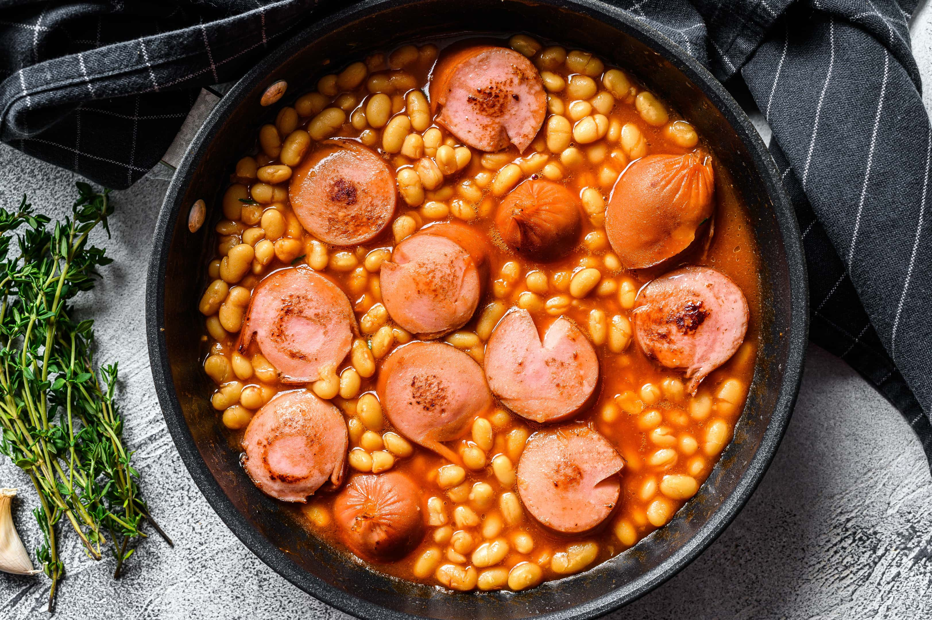 Beans with sausages in tomato sauce in a pan