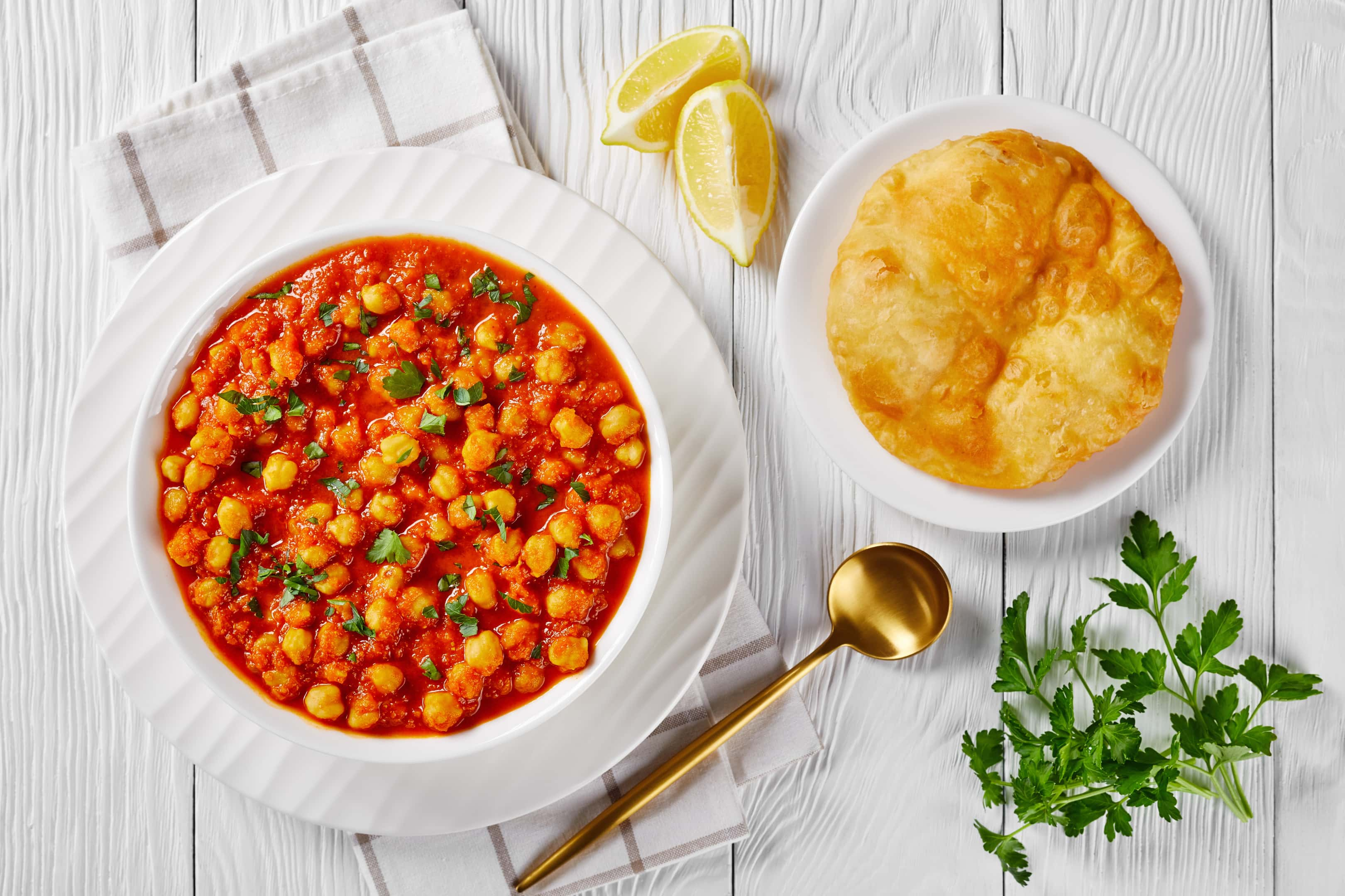 Chana masala chickpea curry with spices and tomato sauce served with indian fried bread bhatura