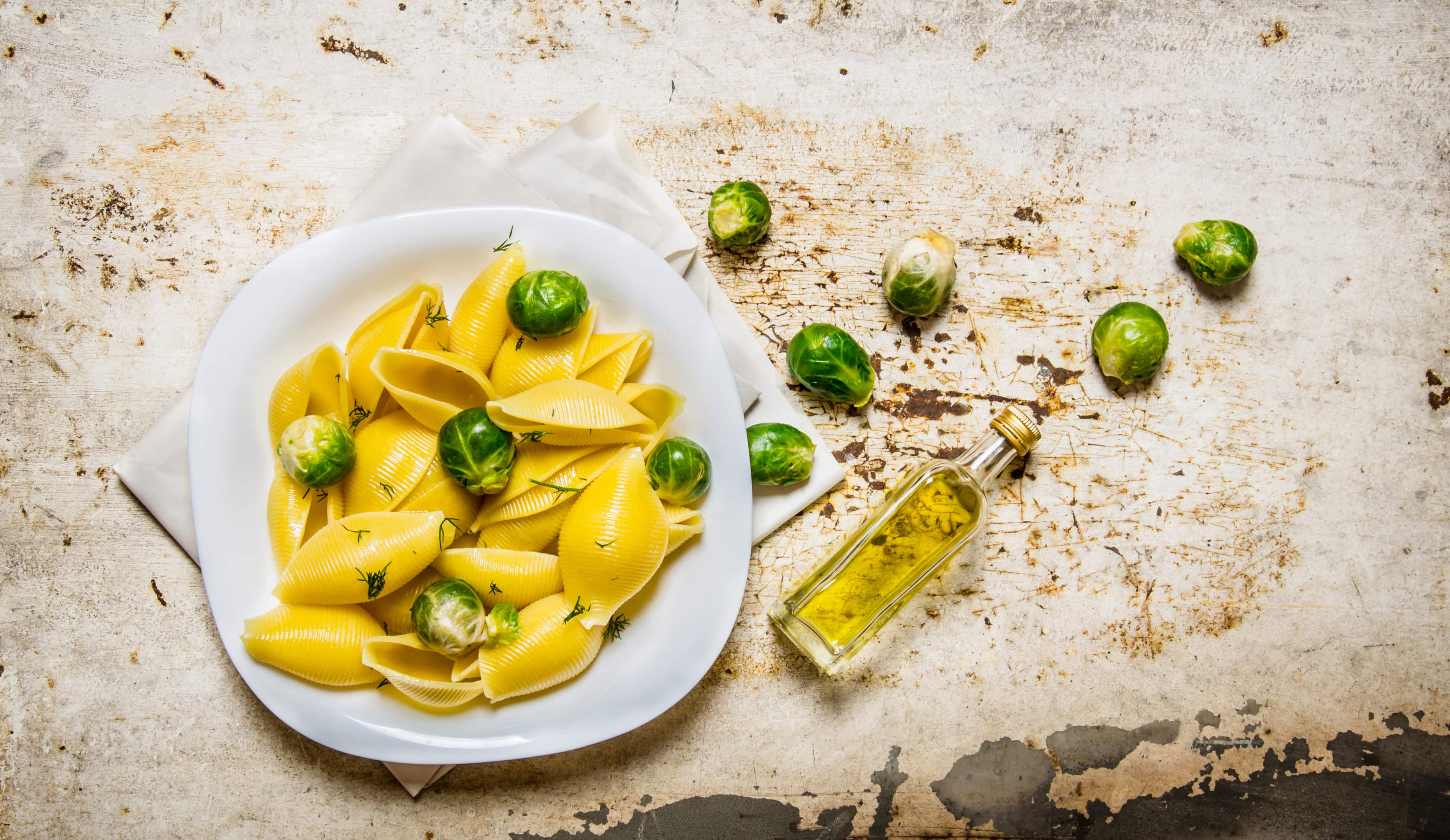 Cooked pasta with brussels sprouts on white plate with olive oil on rustic table