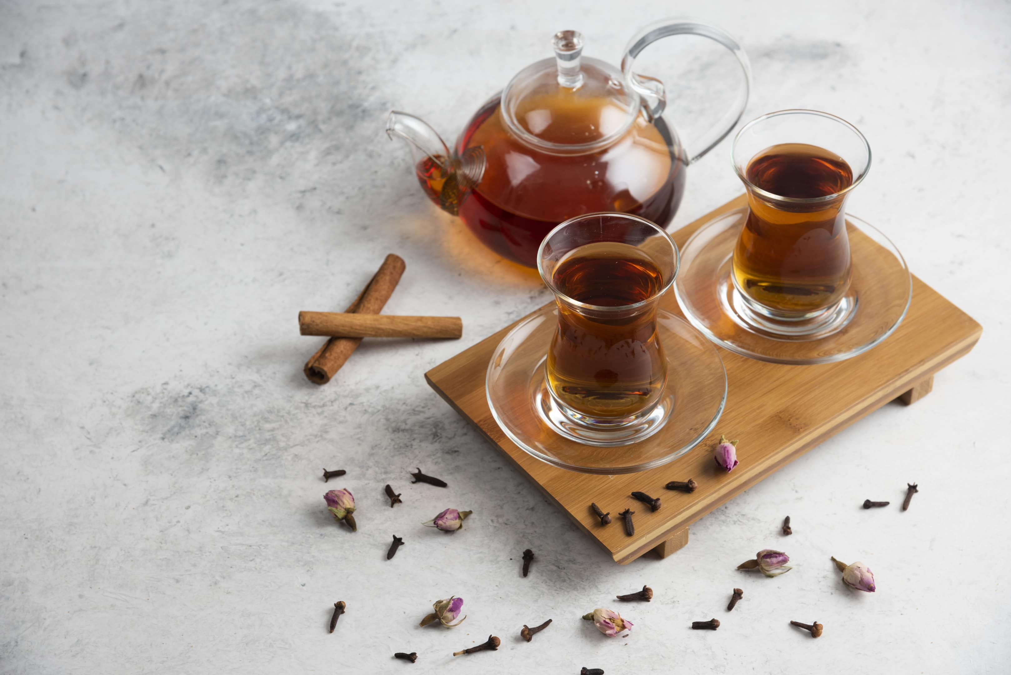 Cups of tea with cloves cinnamon sticks and dried roses