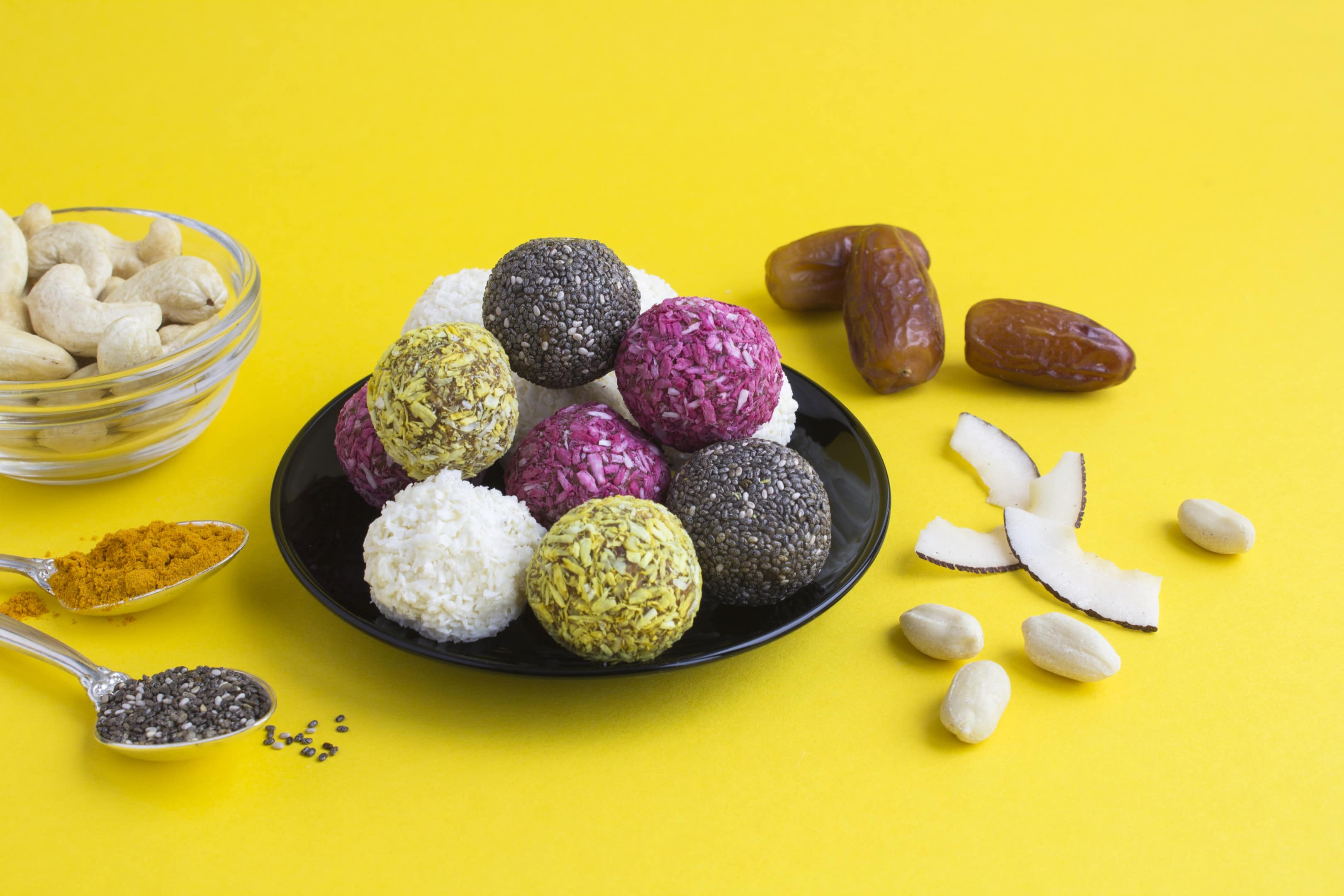 Energy balls of seeds and nuts on black plate on yellow background