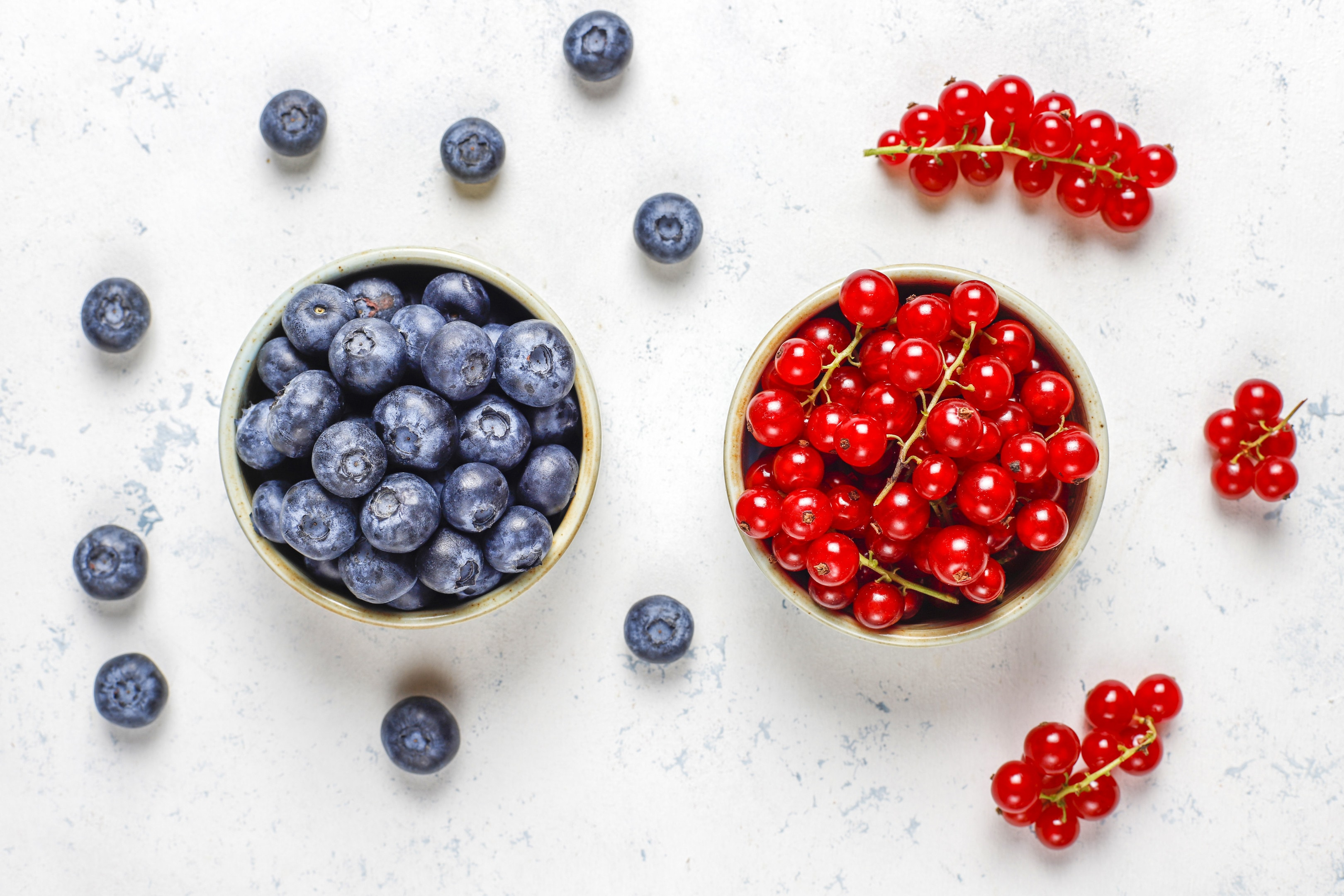 Fresh blueberries and cranberries on white table