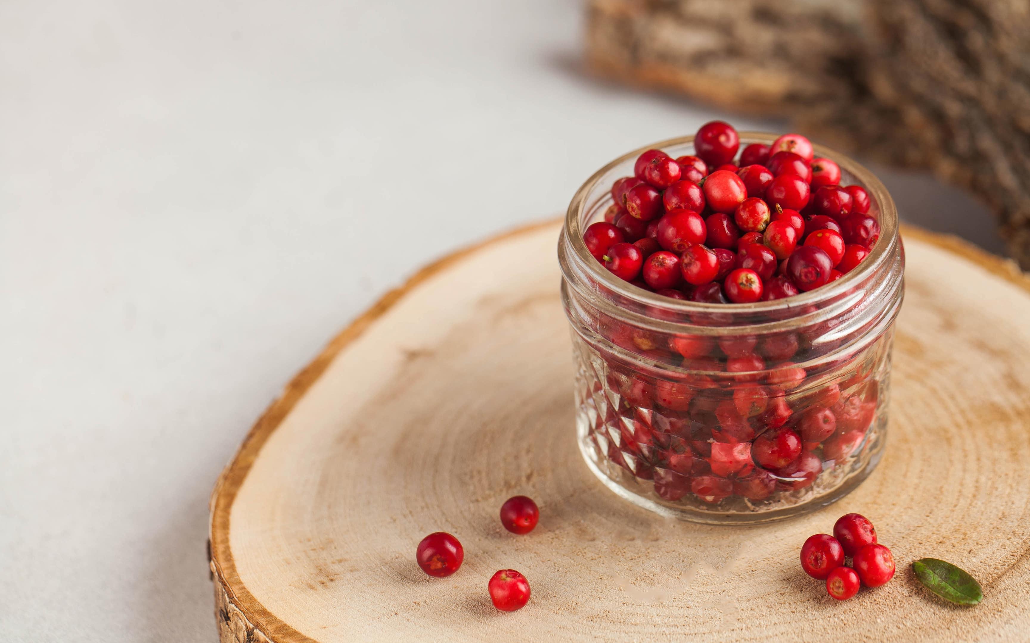 Fresh ripe cranberries in glass jar on wooden board