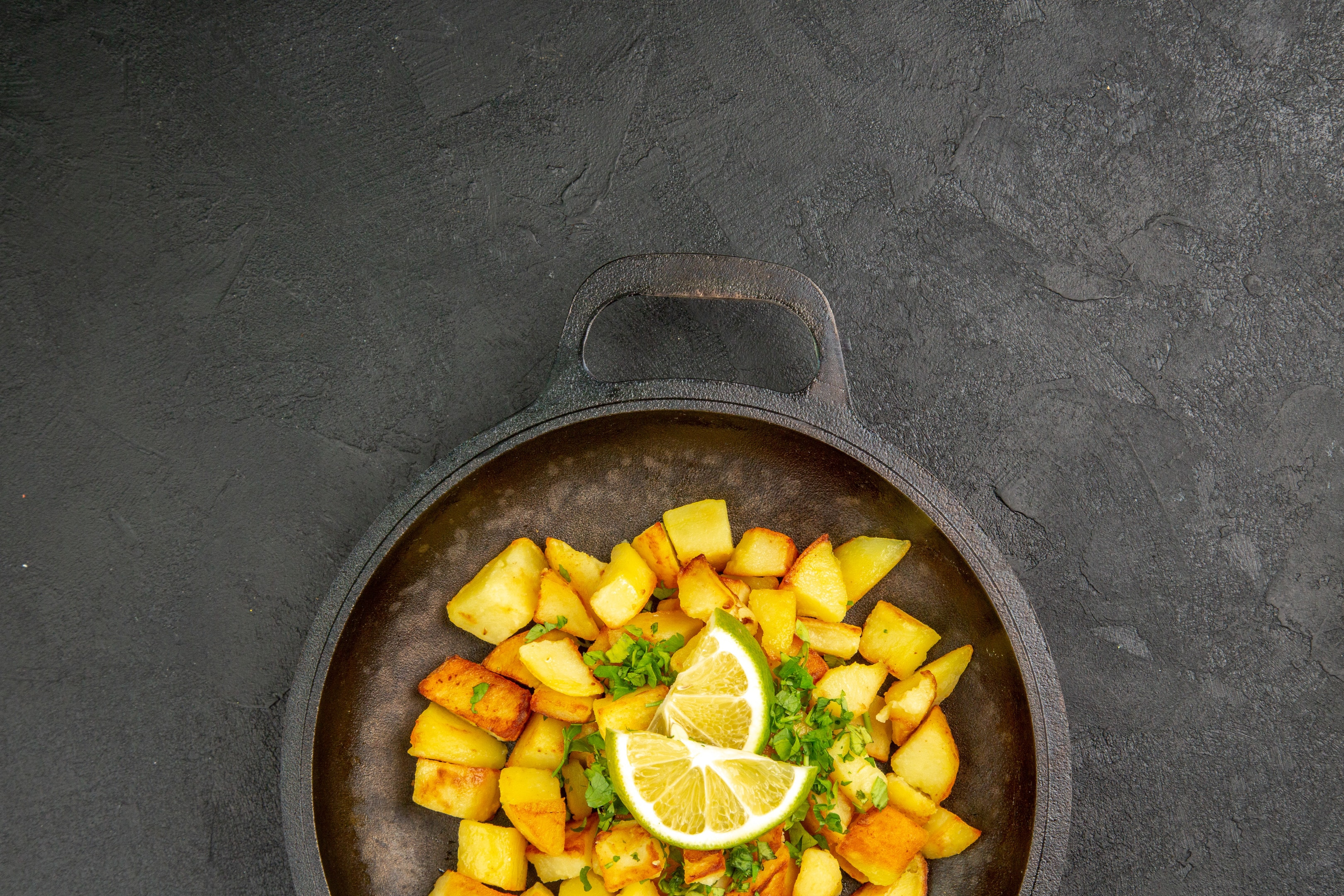 Fried potatoes in a pan with lemon slices on dark surface