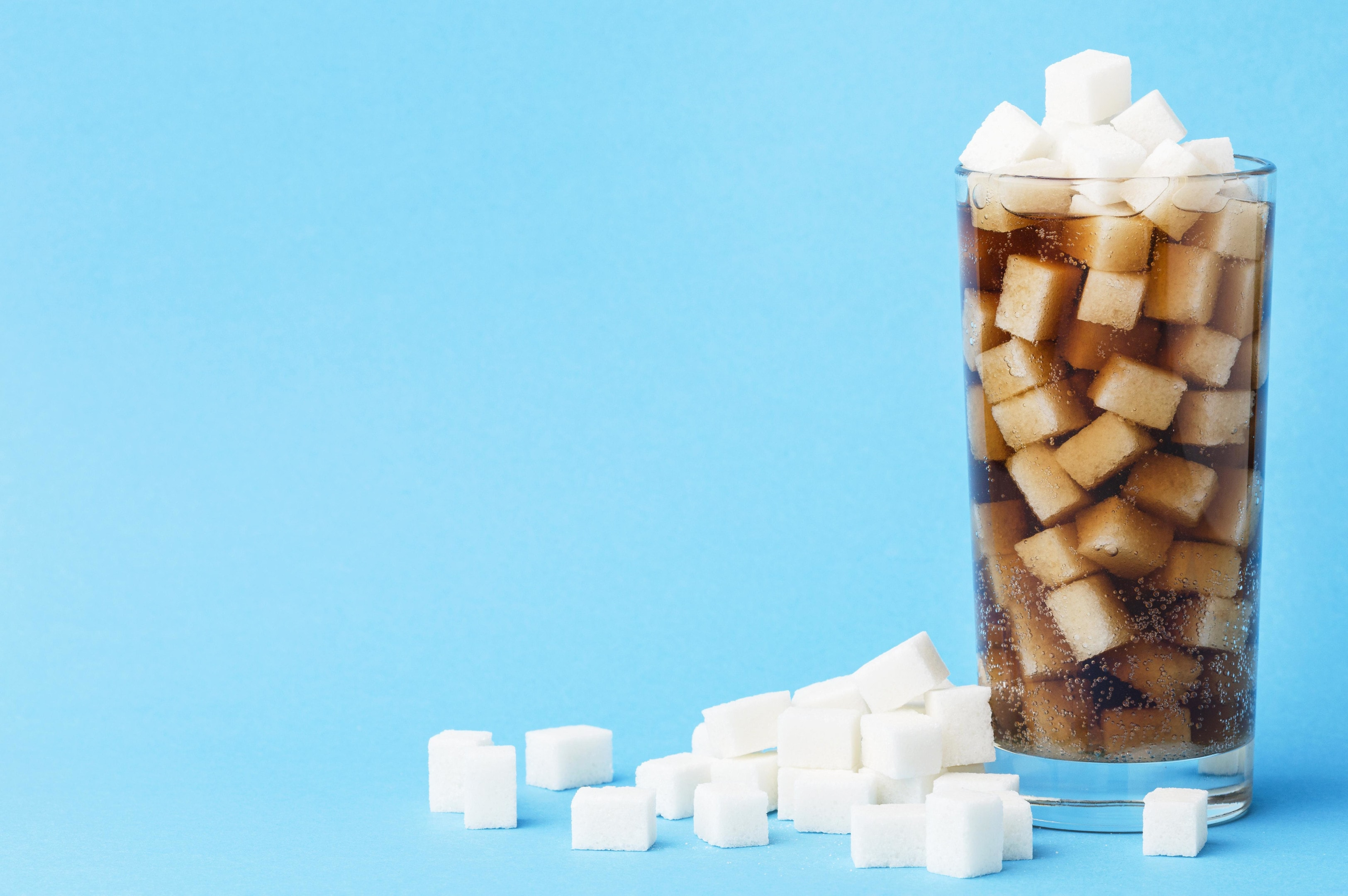 Glass of soft drink with sugar cubes