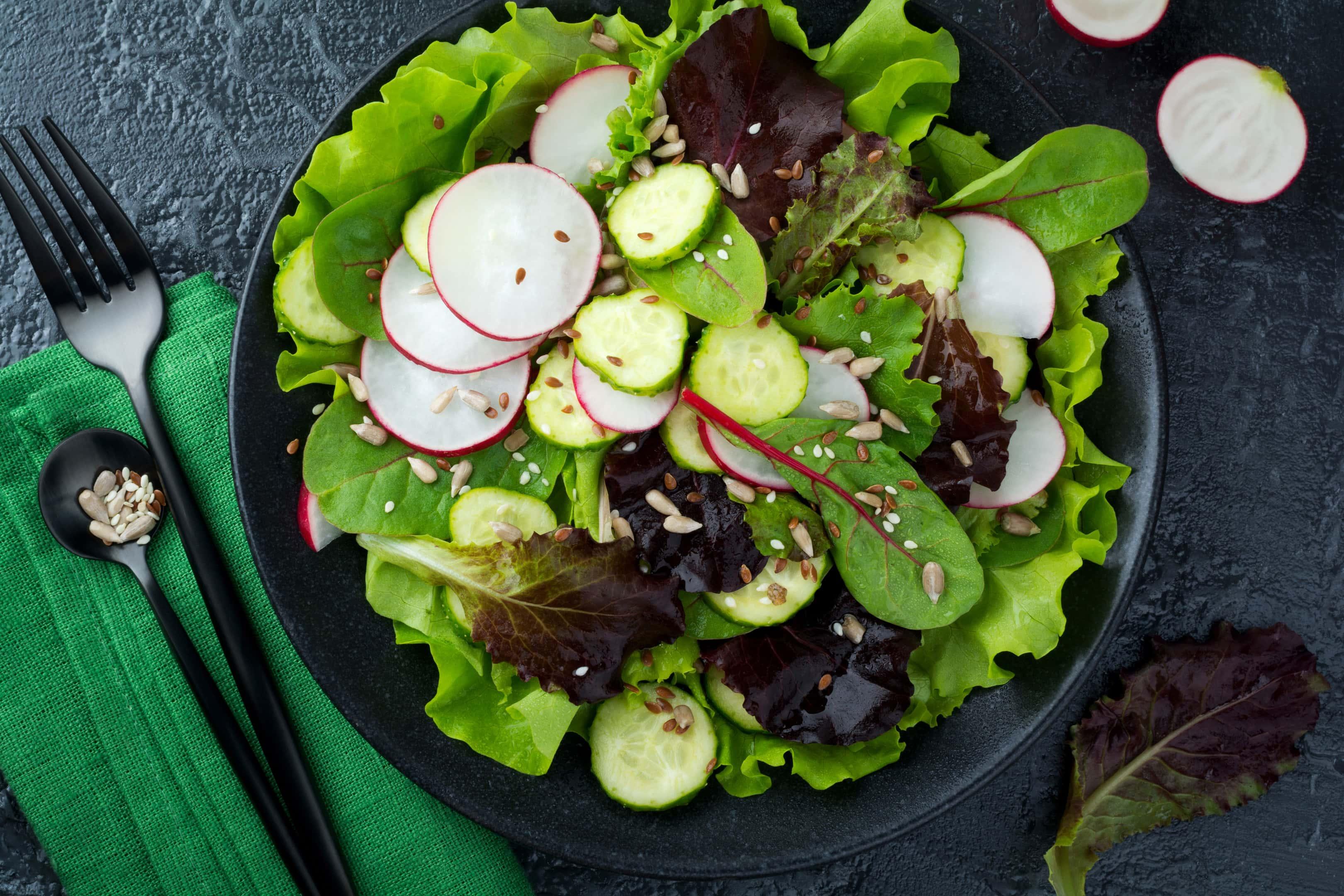 Green salad with fresh radishes arugula sunflower flax and sesame seeds