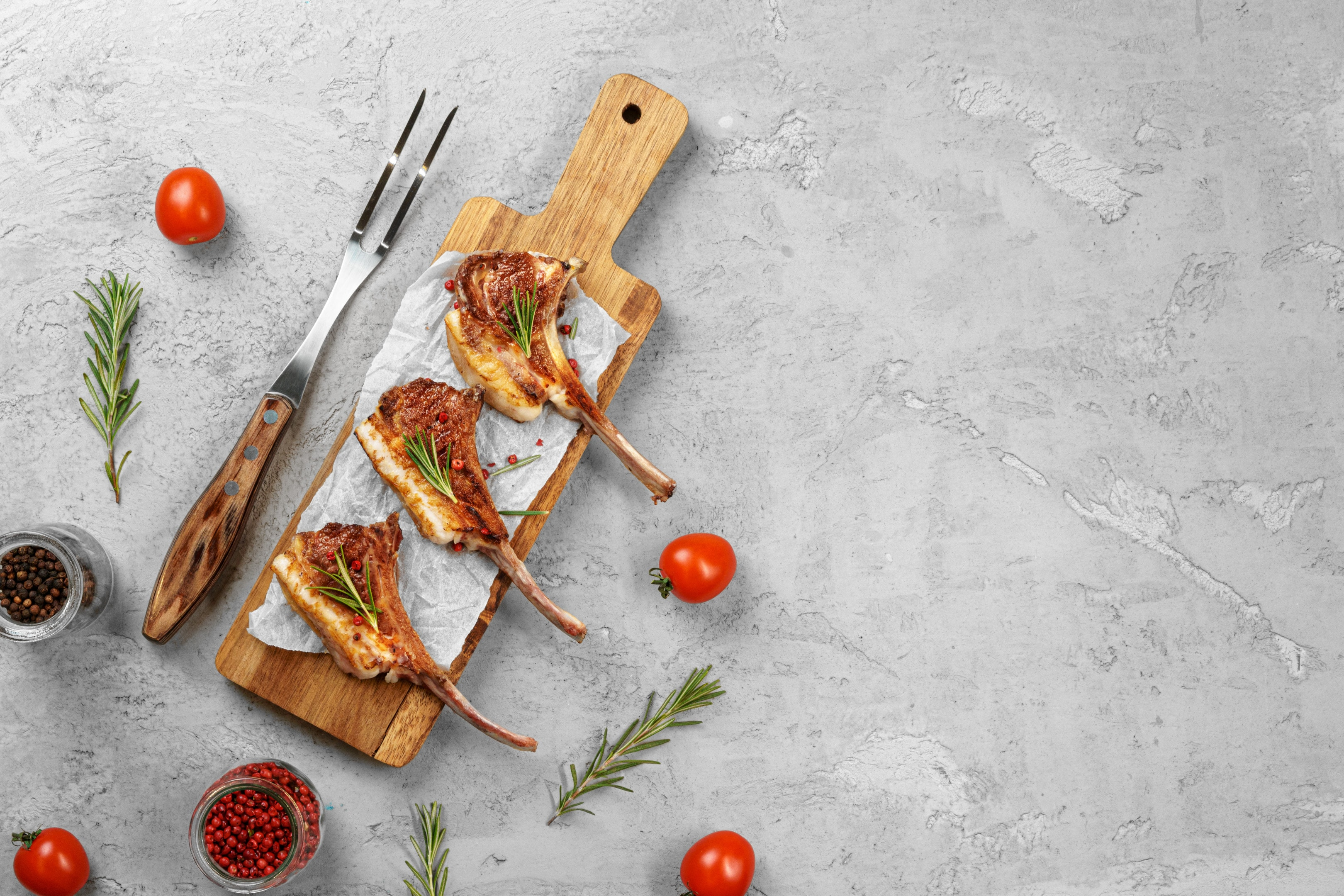 Grilled rack of lamb served on wooden board