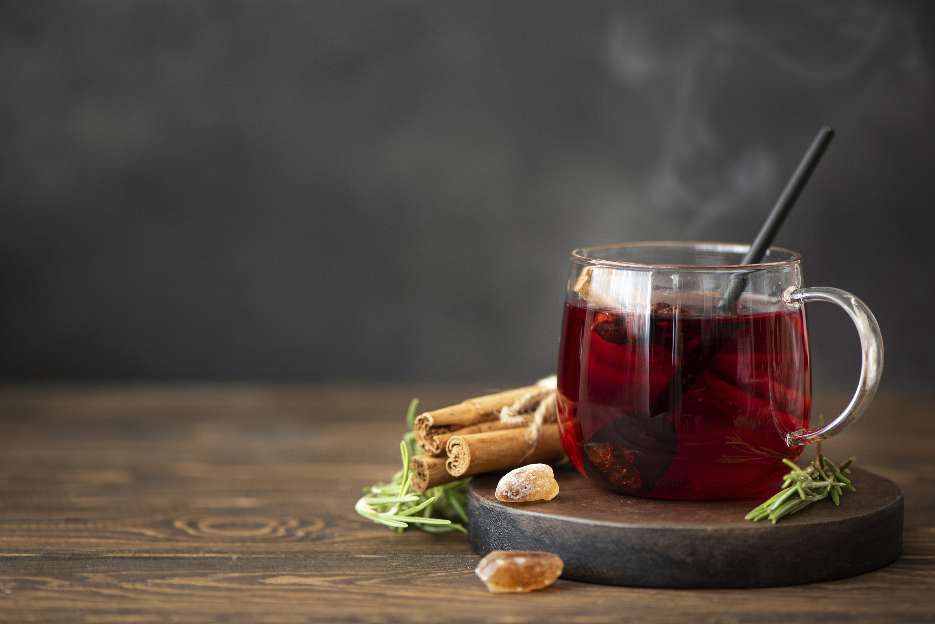 Hot hibiscus tea with cinnamon on wooden table