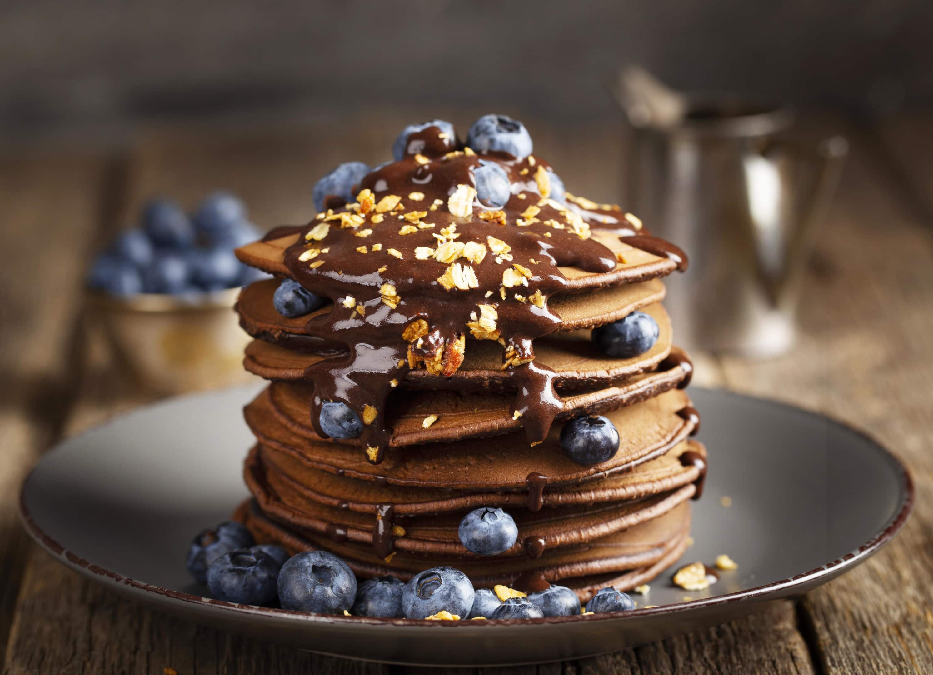 Oat flour pancakes tower with melted chocolate and blueberries