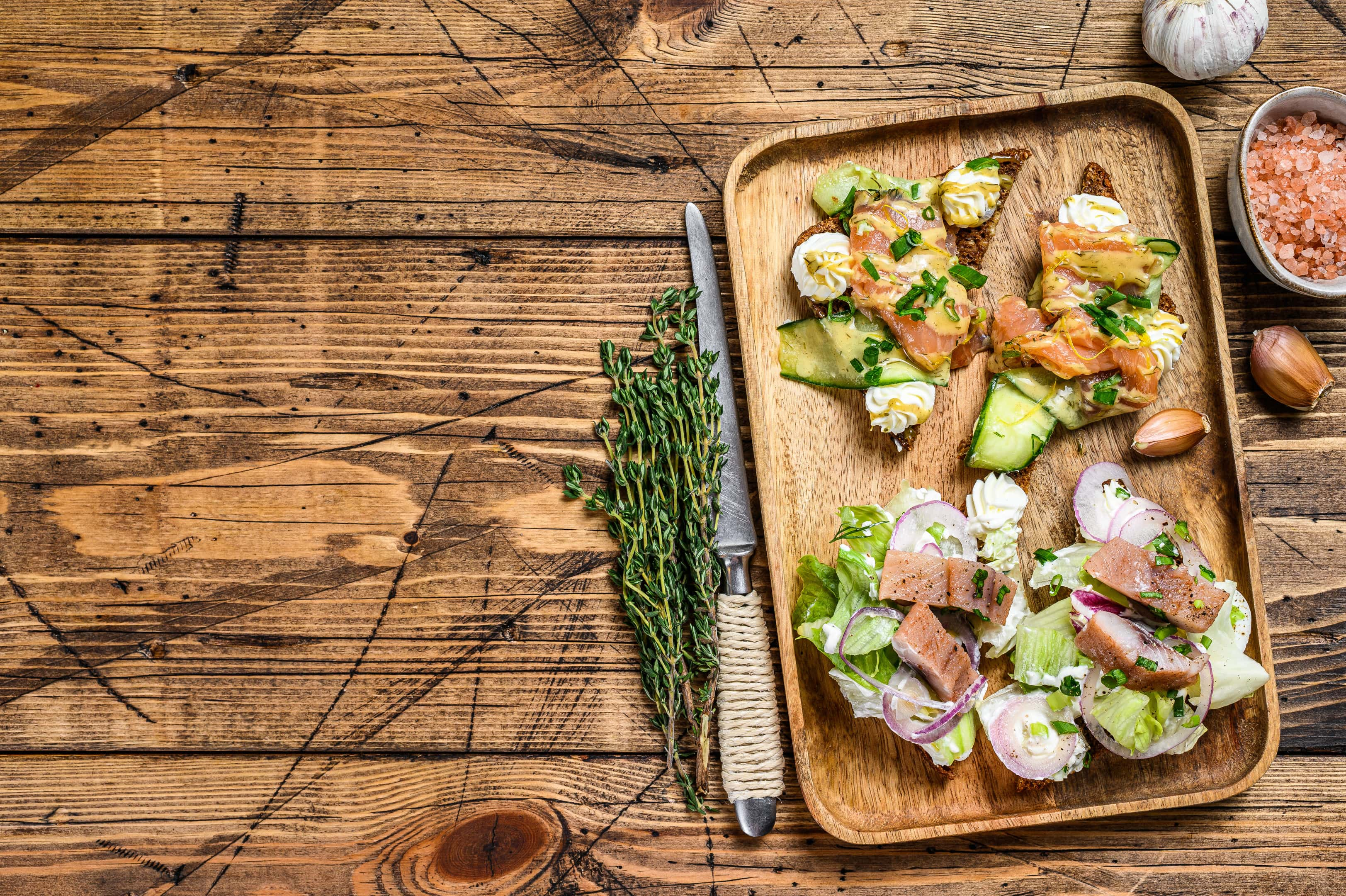 Open sandwich with salmon herring cream cheese and salad on cutting board