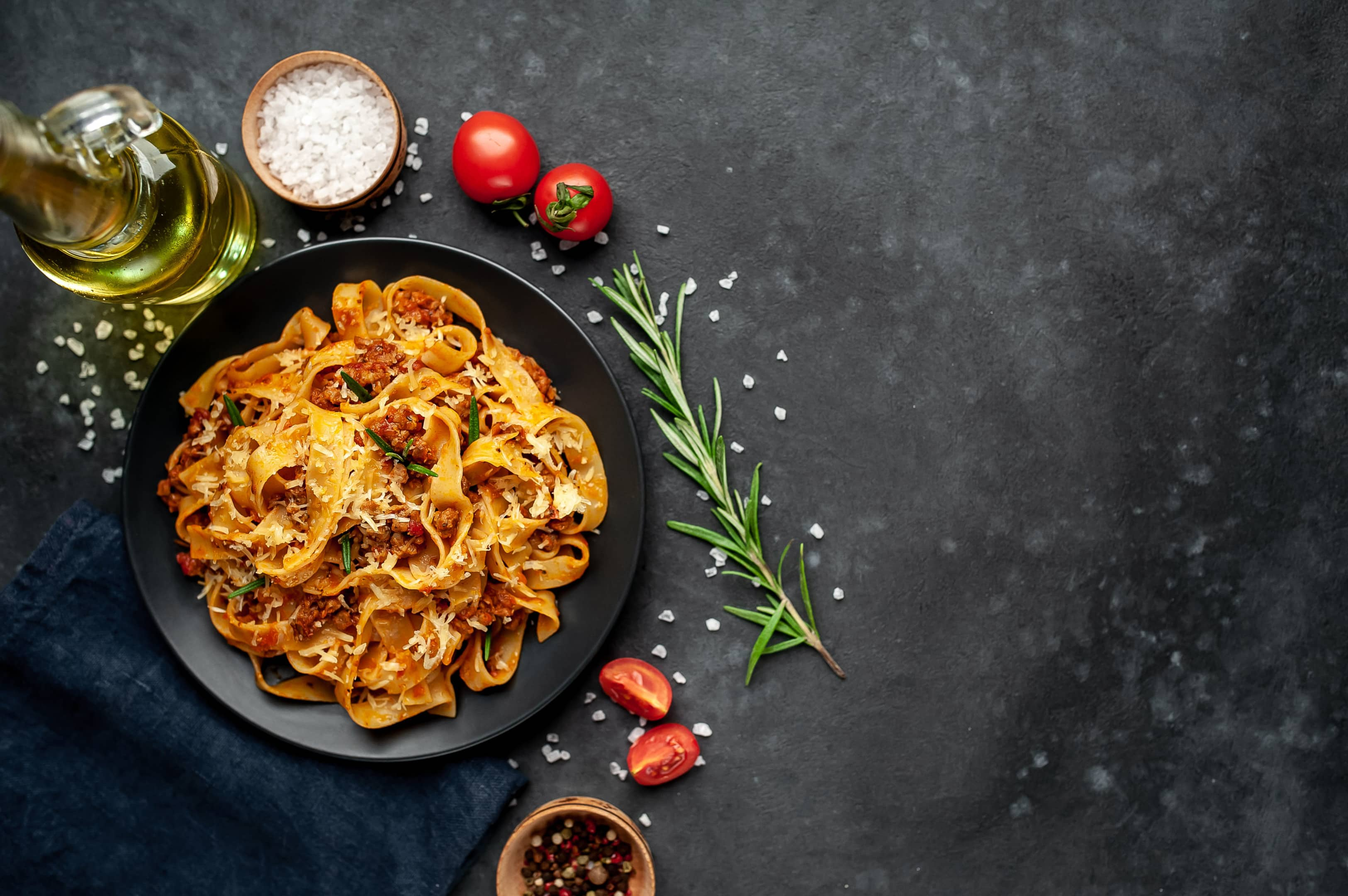 Pasta bolognese with spices on dark plate
