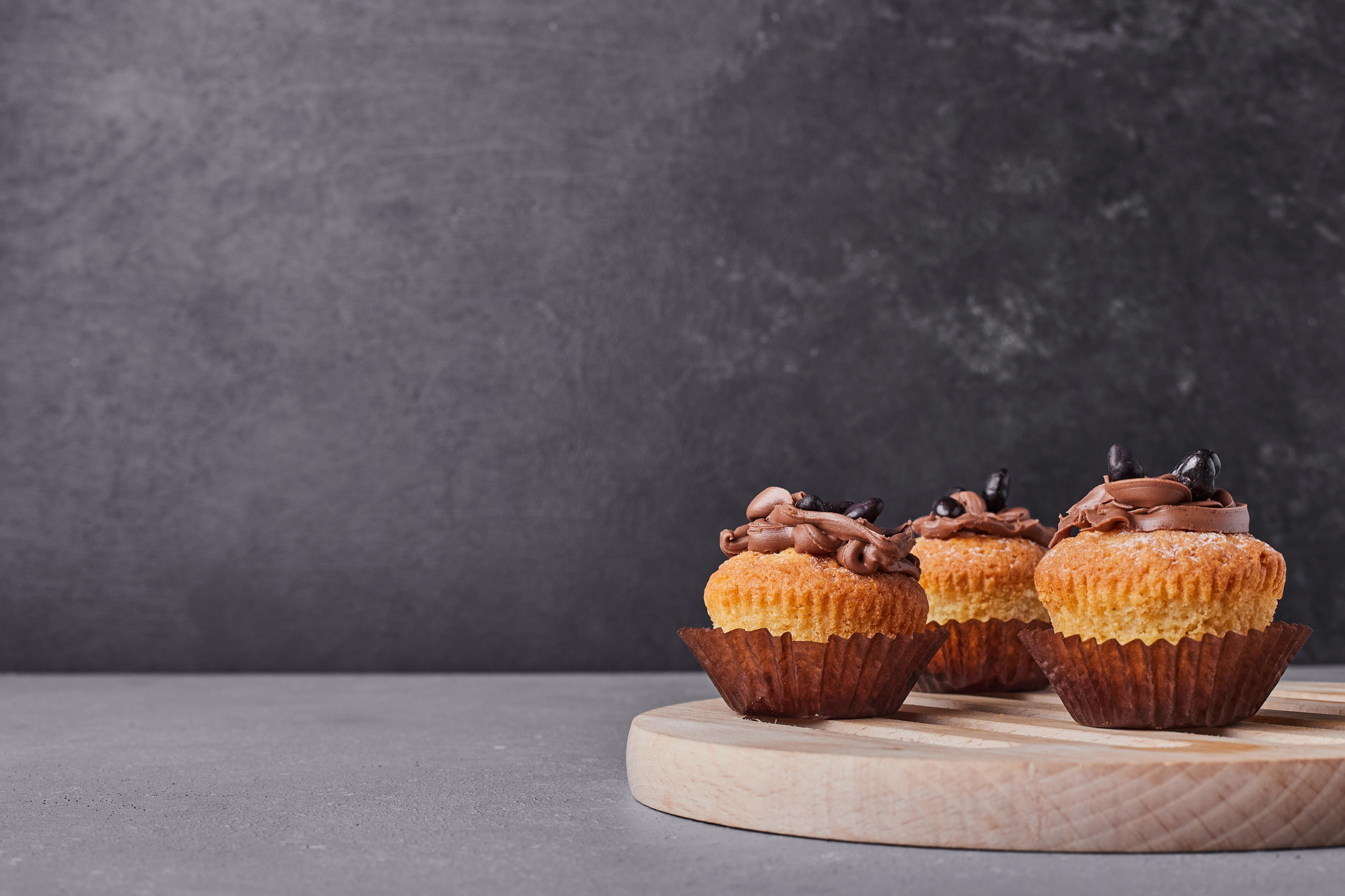 Plantain flour cupcakes with chocolate cream on wooden platter