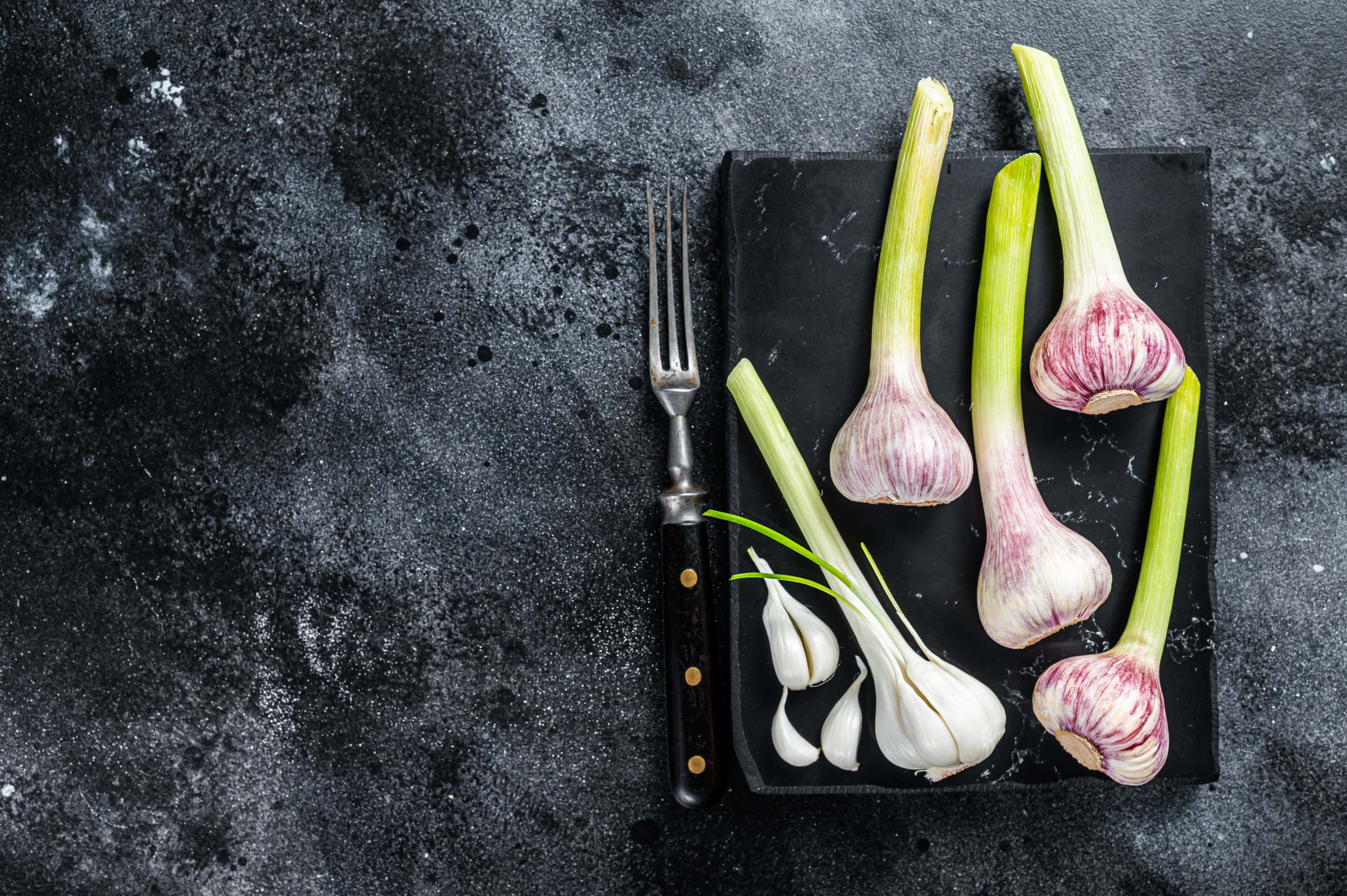 Raw spring of young garlic on marble board