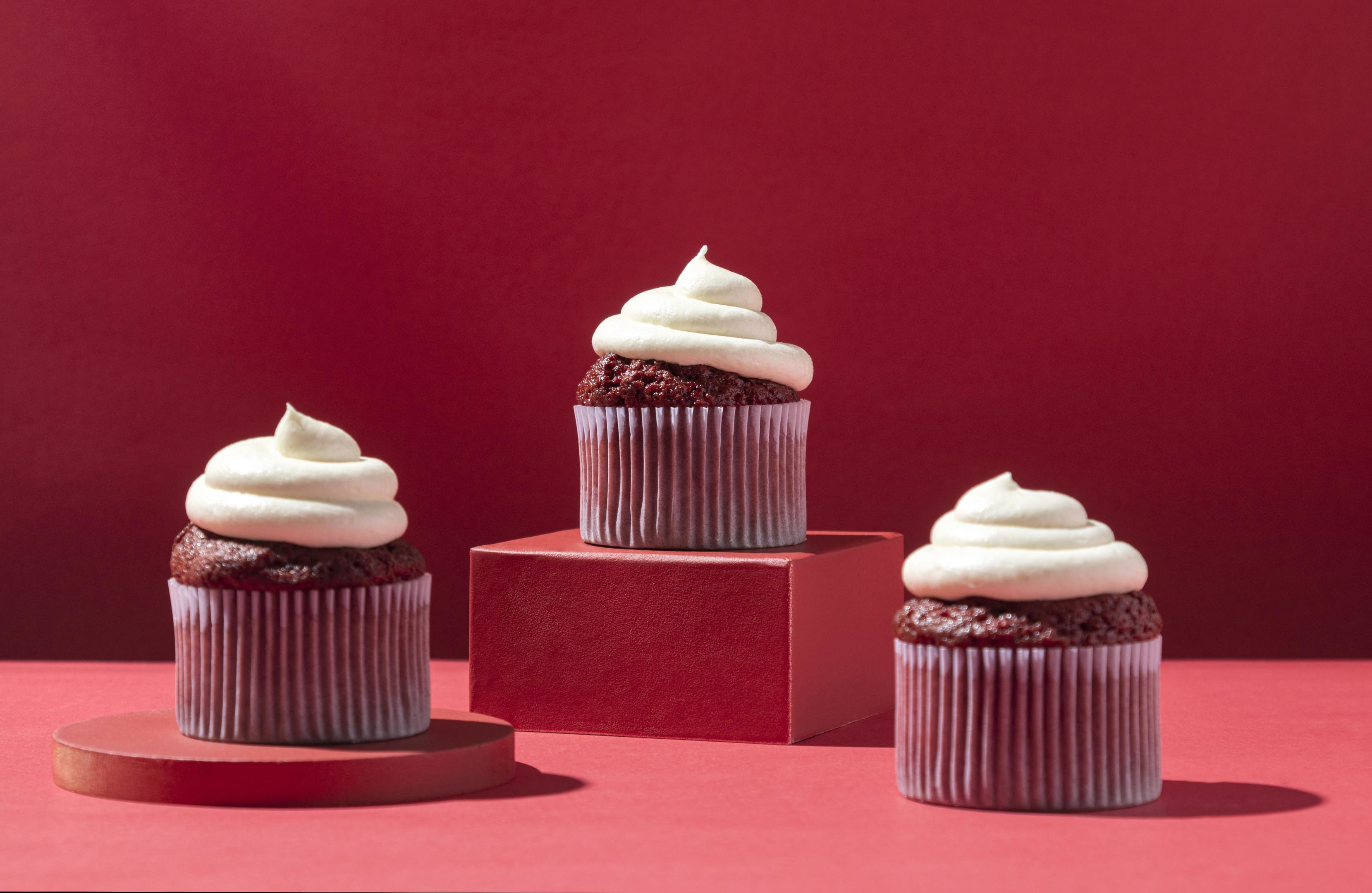 Red velvet cupcakes with cream on red background