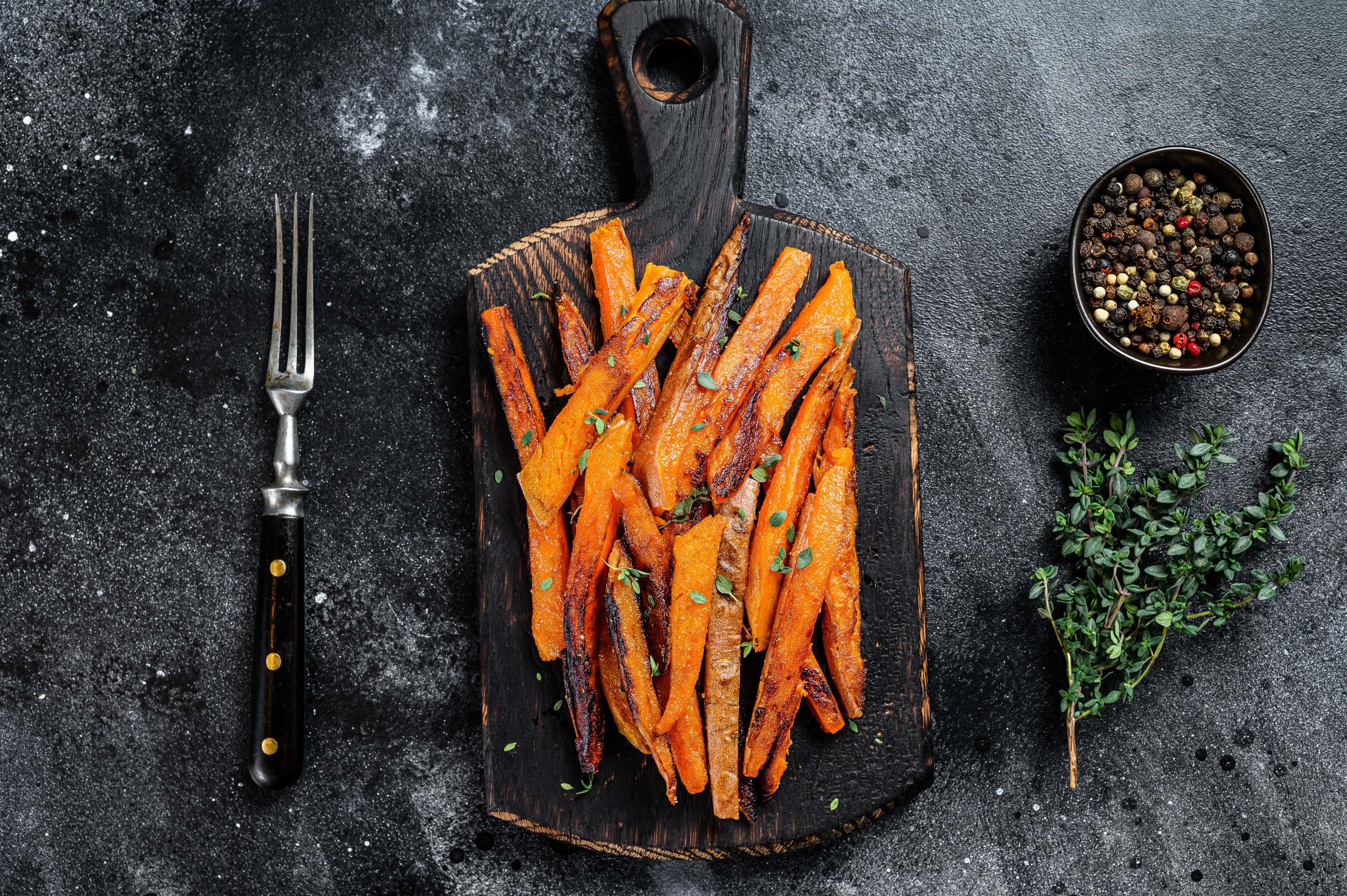 Roasted sweet potatoes stripes on wooden board