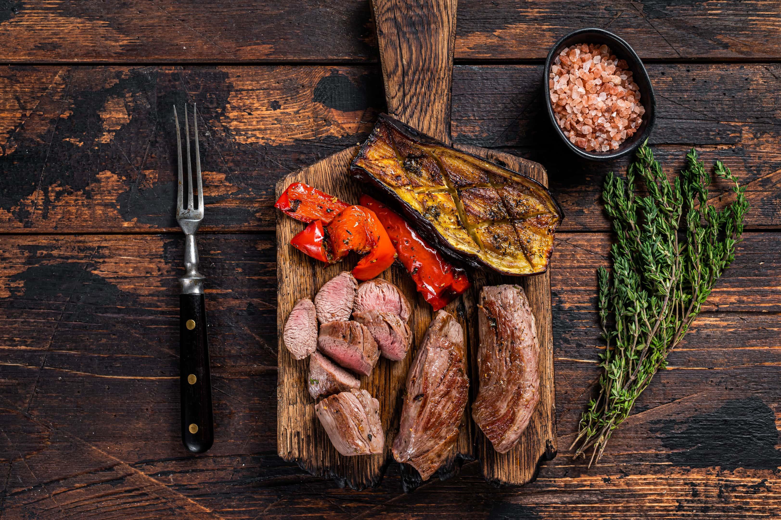 Roasted venison tenderloin fillet on wooden cutting board