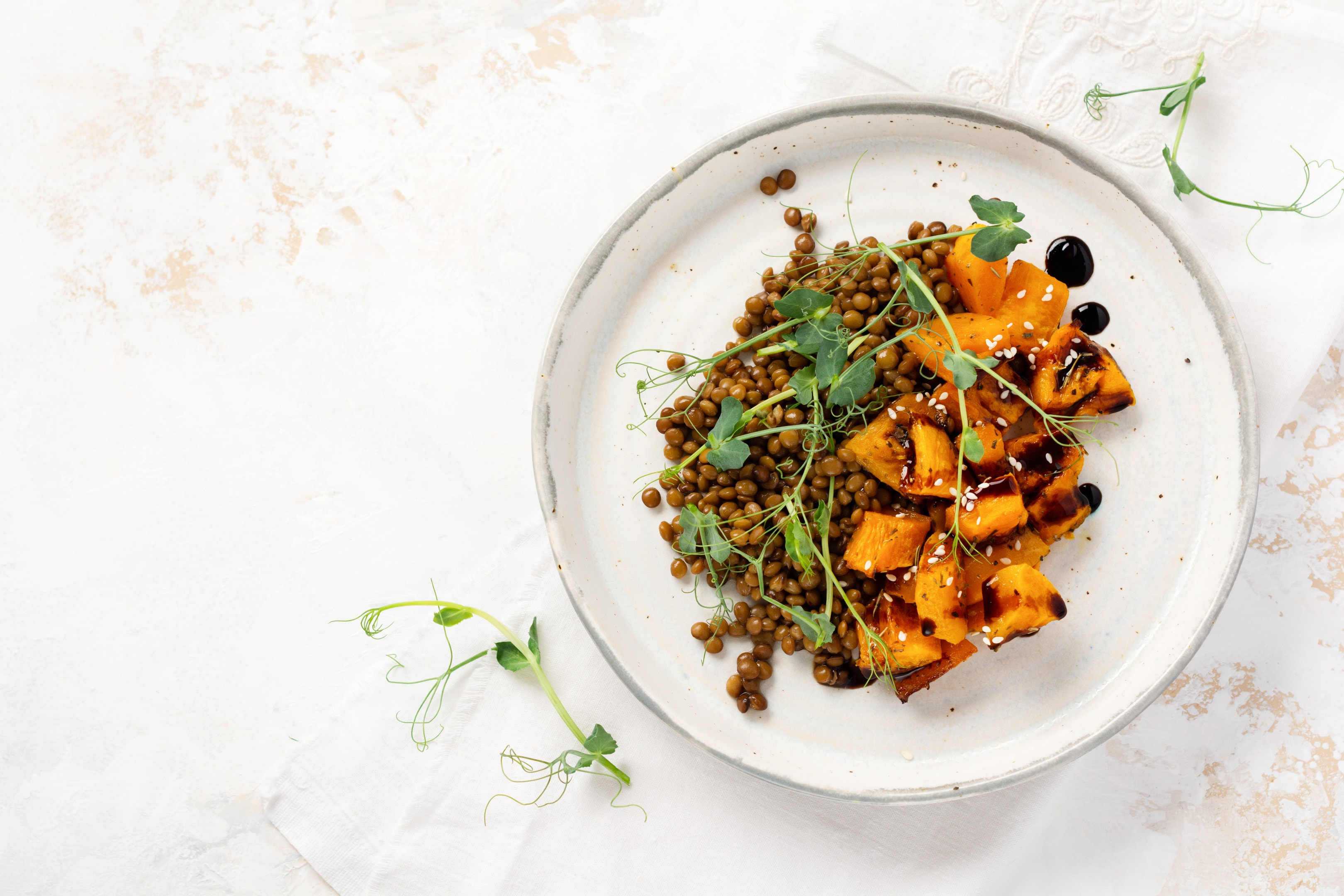 Salad with baked pumpkin lentils balsamic dressing garnished with peas microgreens