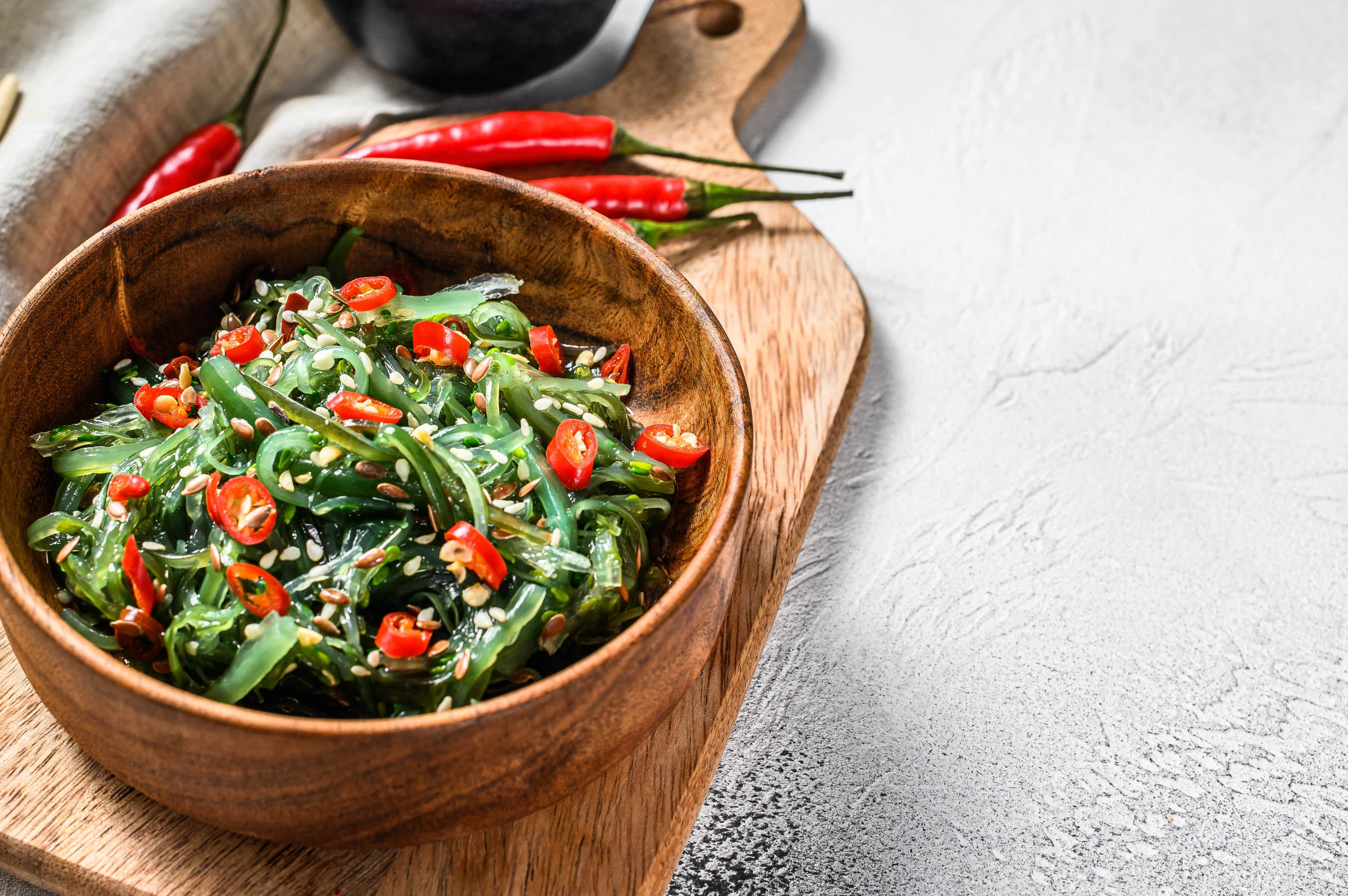 Salad with seaweed wakame and red chili pepper in wooden bowl