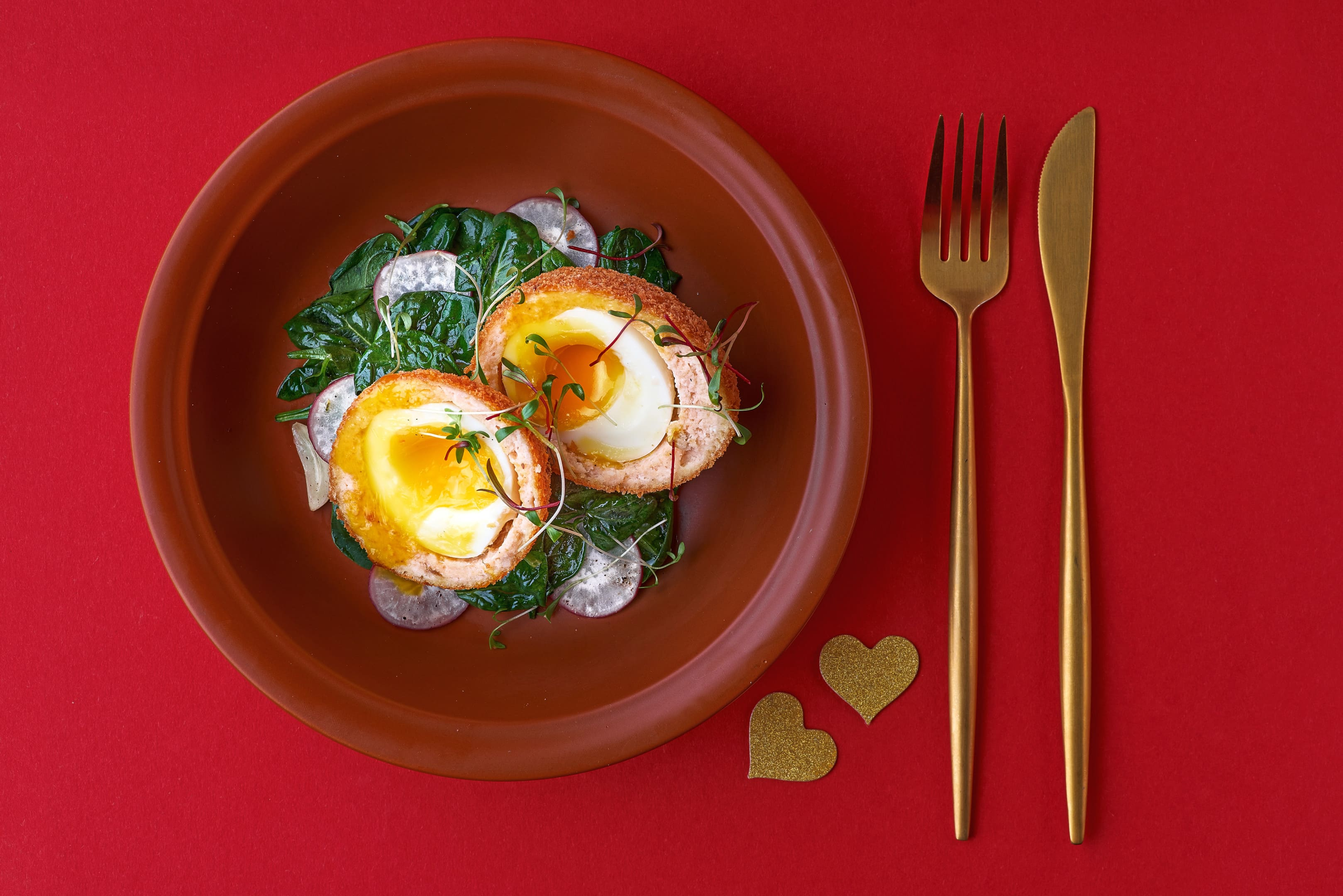 Scotch eggs with salmon radish and spinach on plate