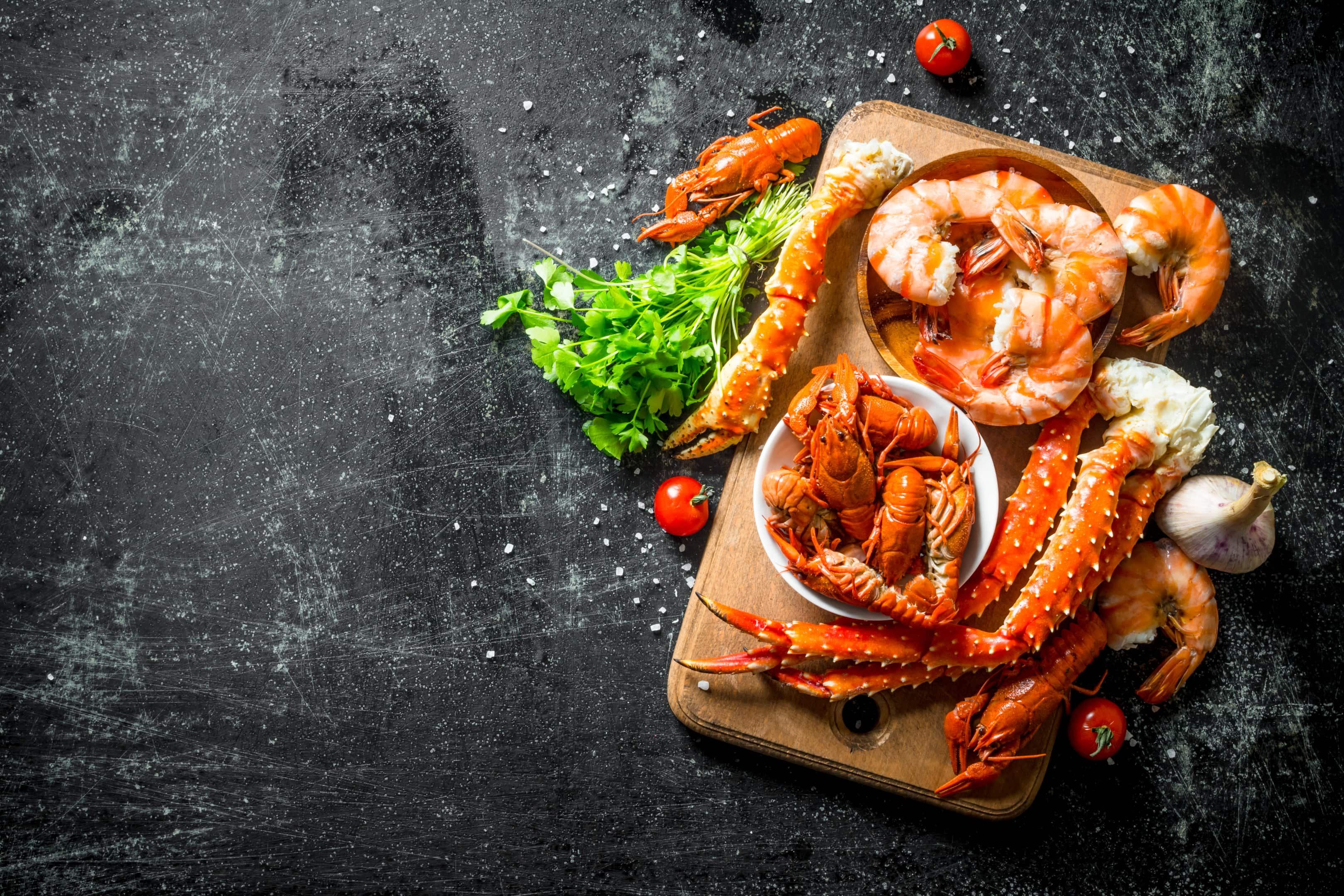 Seafood fragrant shrimp crayfish and crab on wooden board with herbs