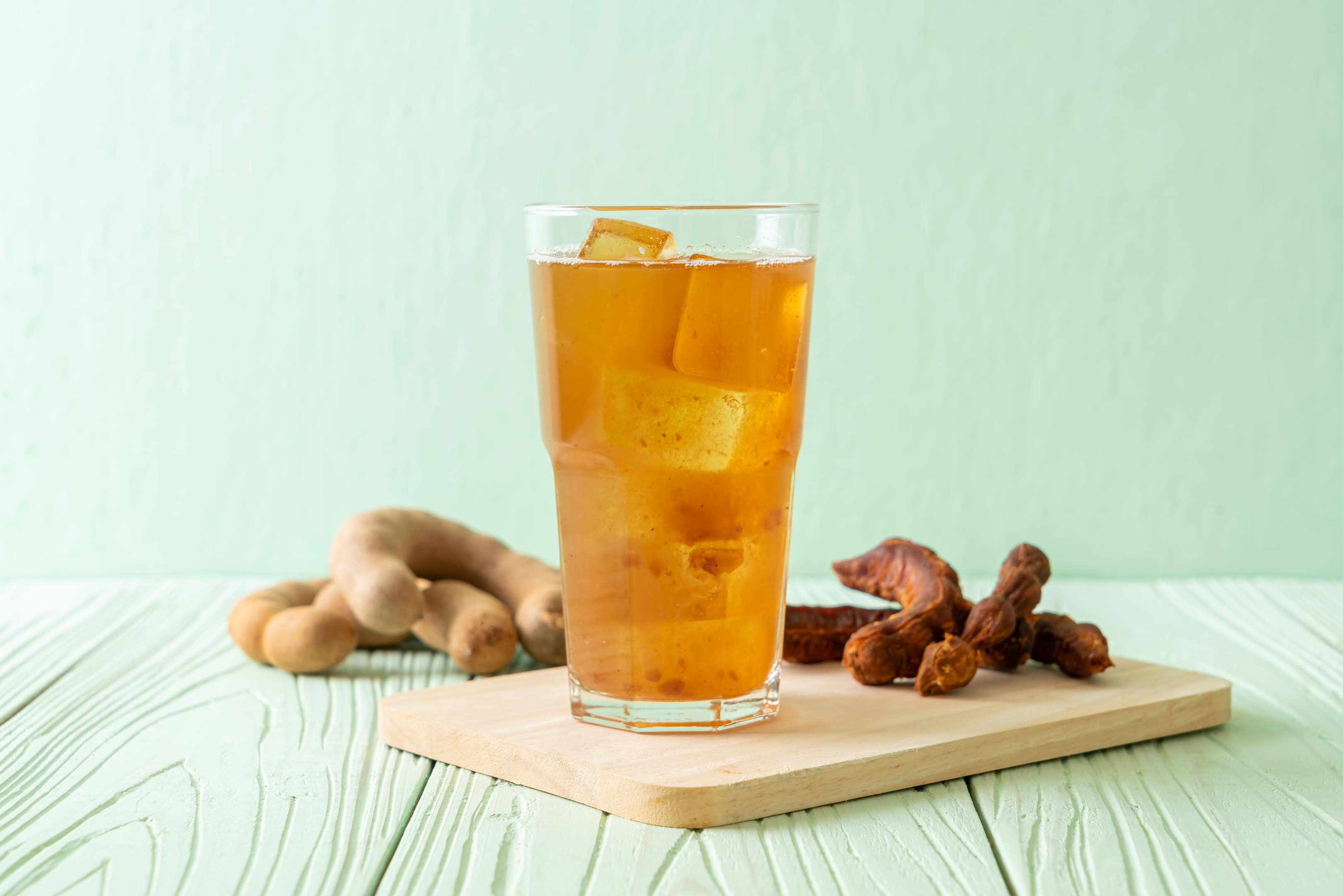 Tamarind and turmeric drink with ice cubes on wooden board