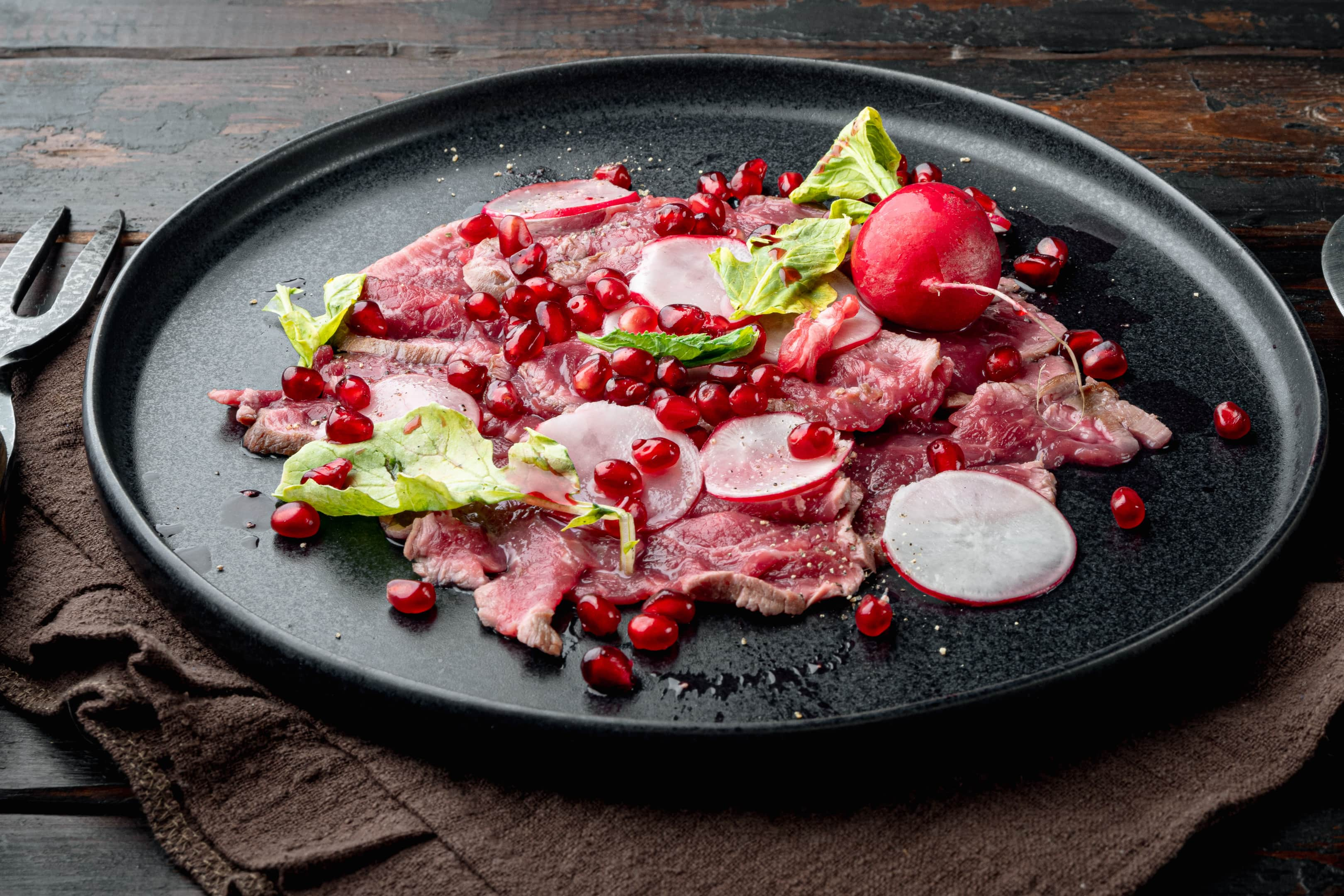 Beef carpaccio with radish, pomegranate seeds and olive oil