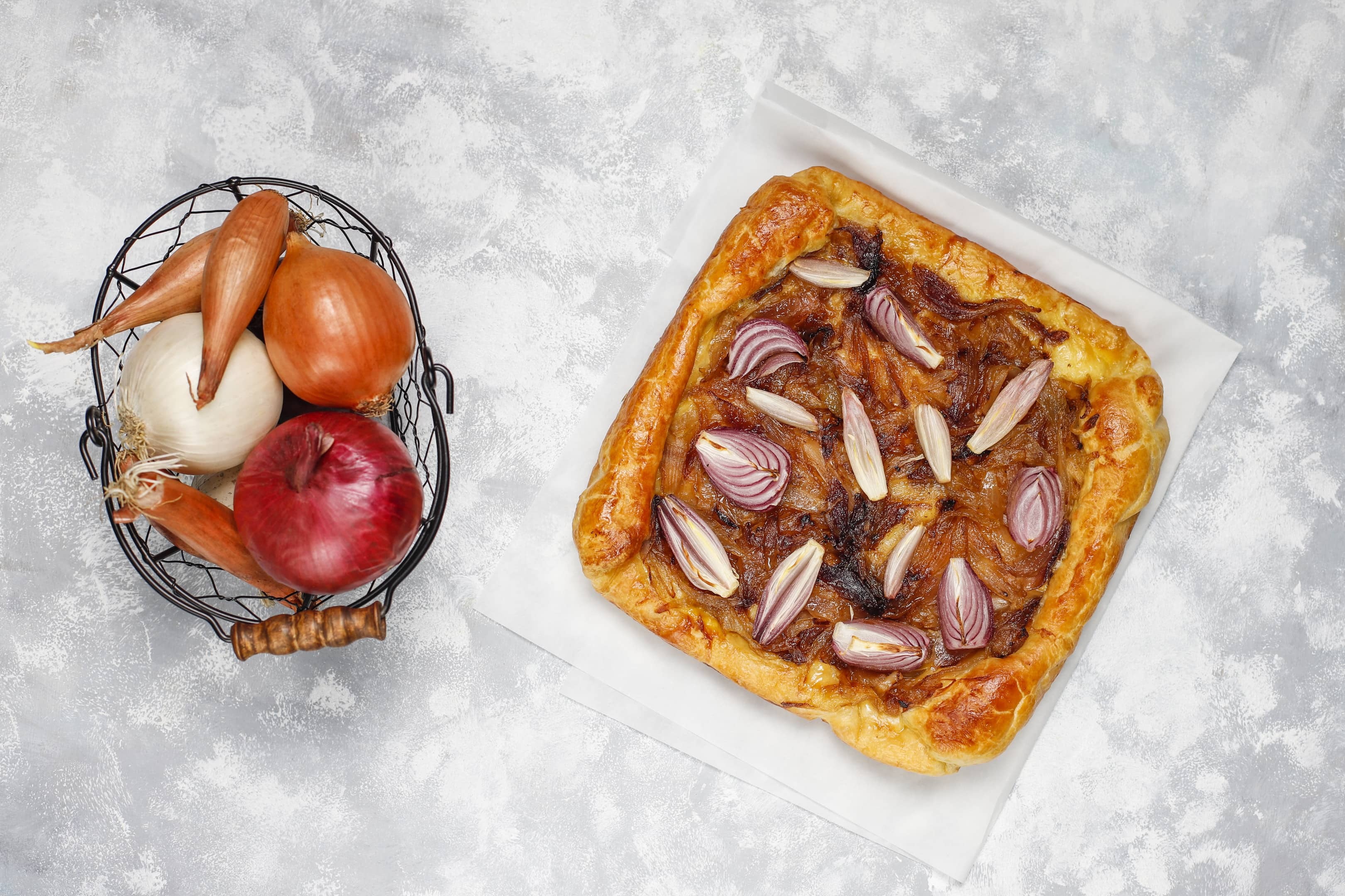 French style onion pie galette with puff pastry and various onions — shallot, red, white and yellow onions