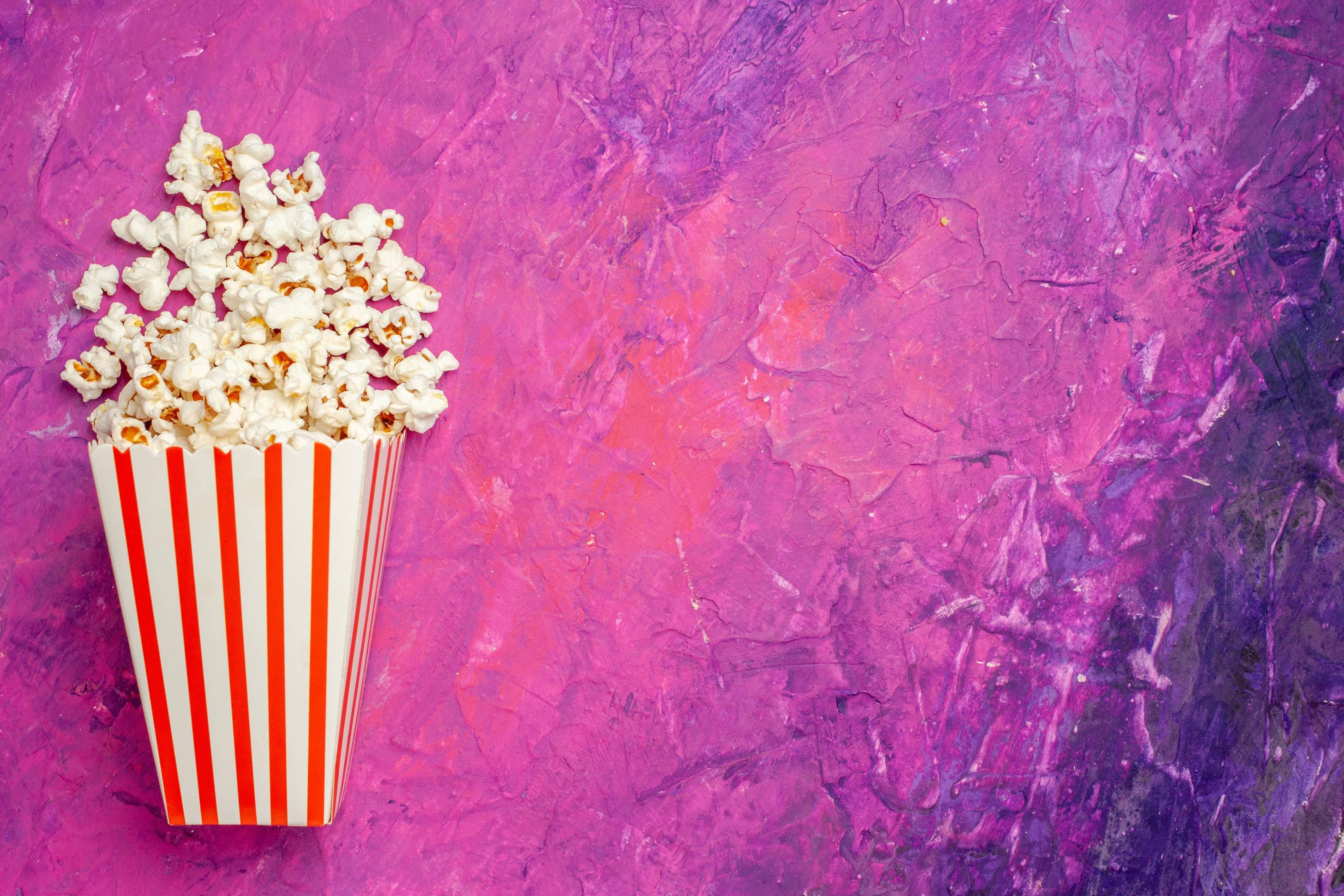 Fresh popcorn bucket on purple background