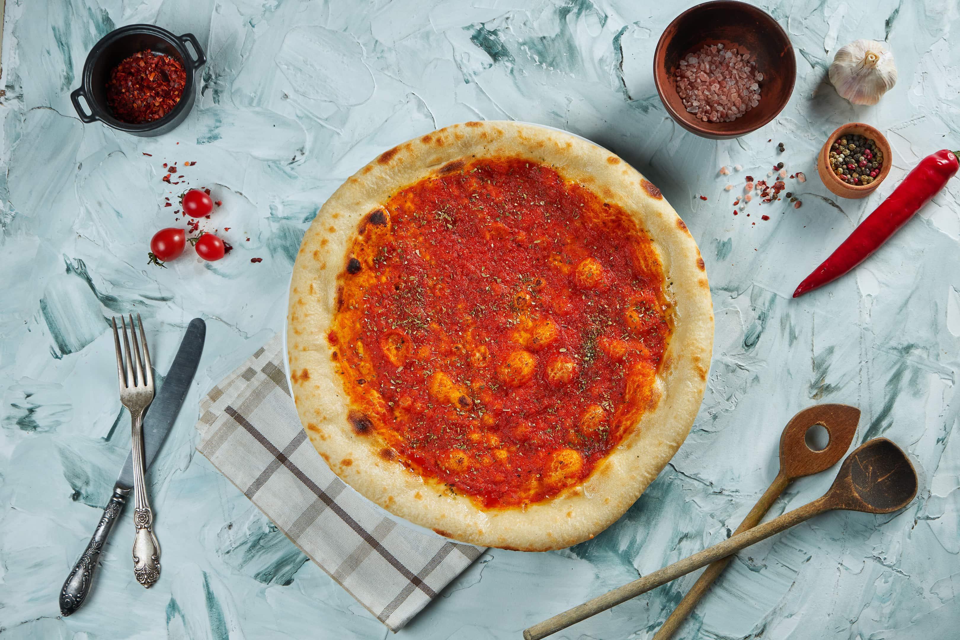 Freshly baked pizza marinara on a gray table
