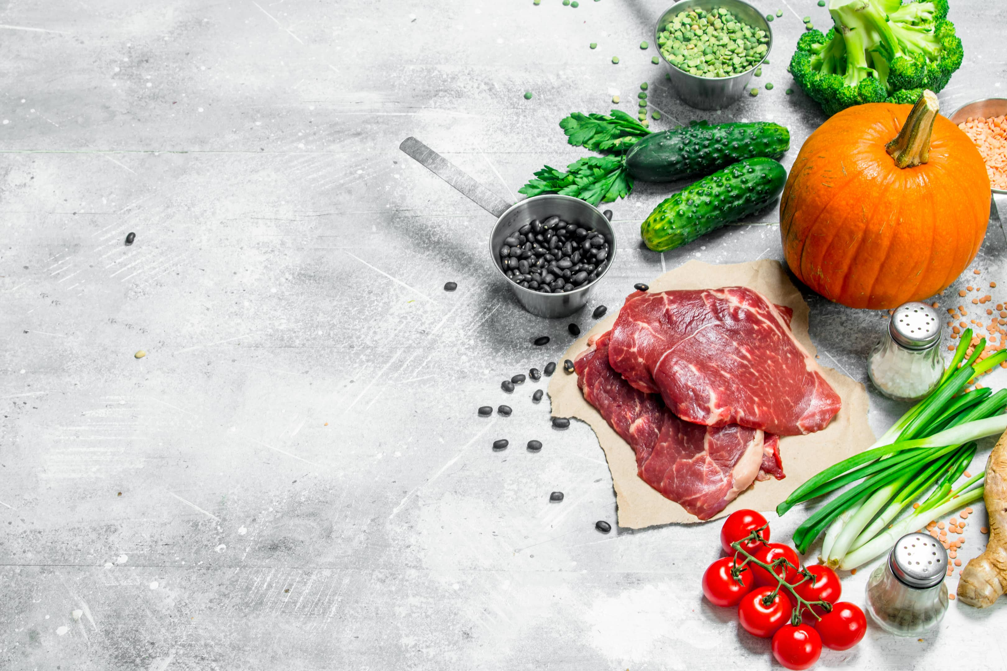 Healthy foods — raw lean beef, seeds, legumes and leafy vegetables