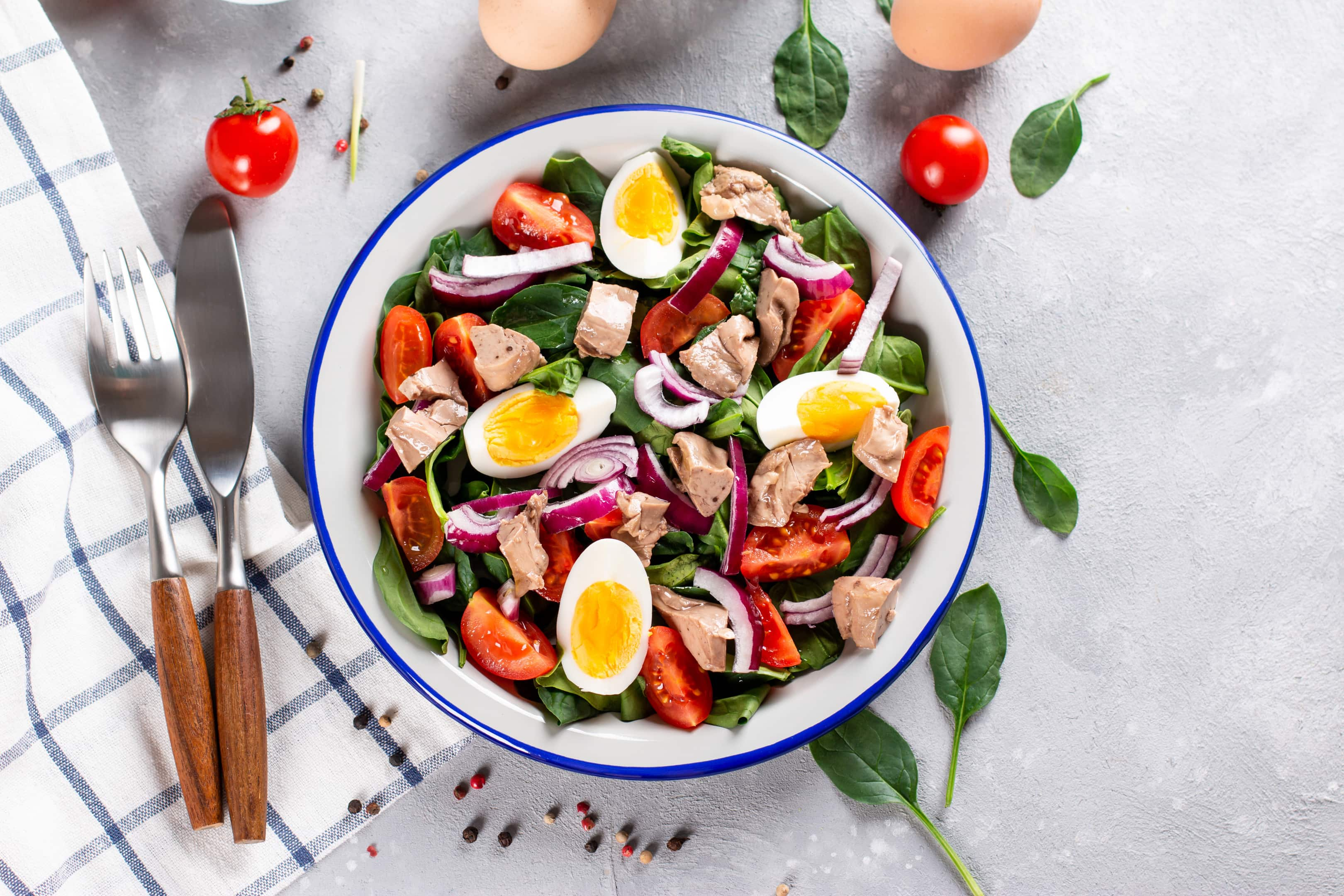 Salad of codfish liver with eggs, spinach and tomato