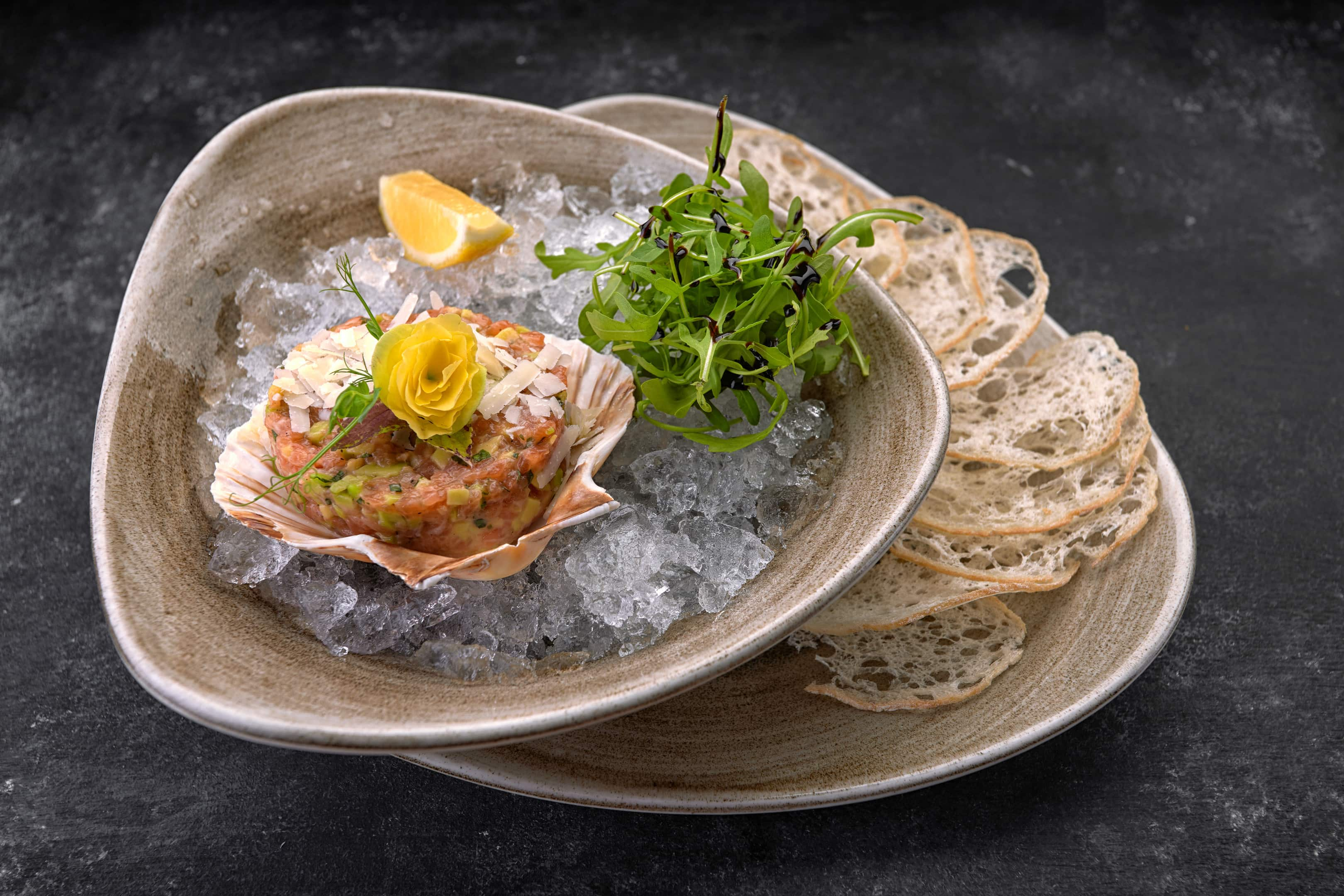 Salmon tartare with oysters, avocado, bread chips and lemon