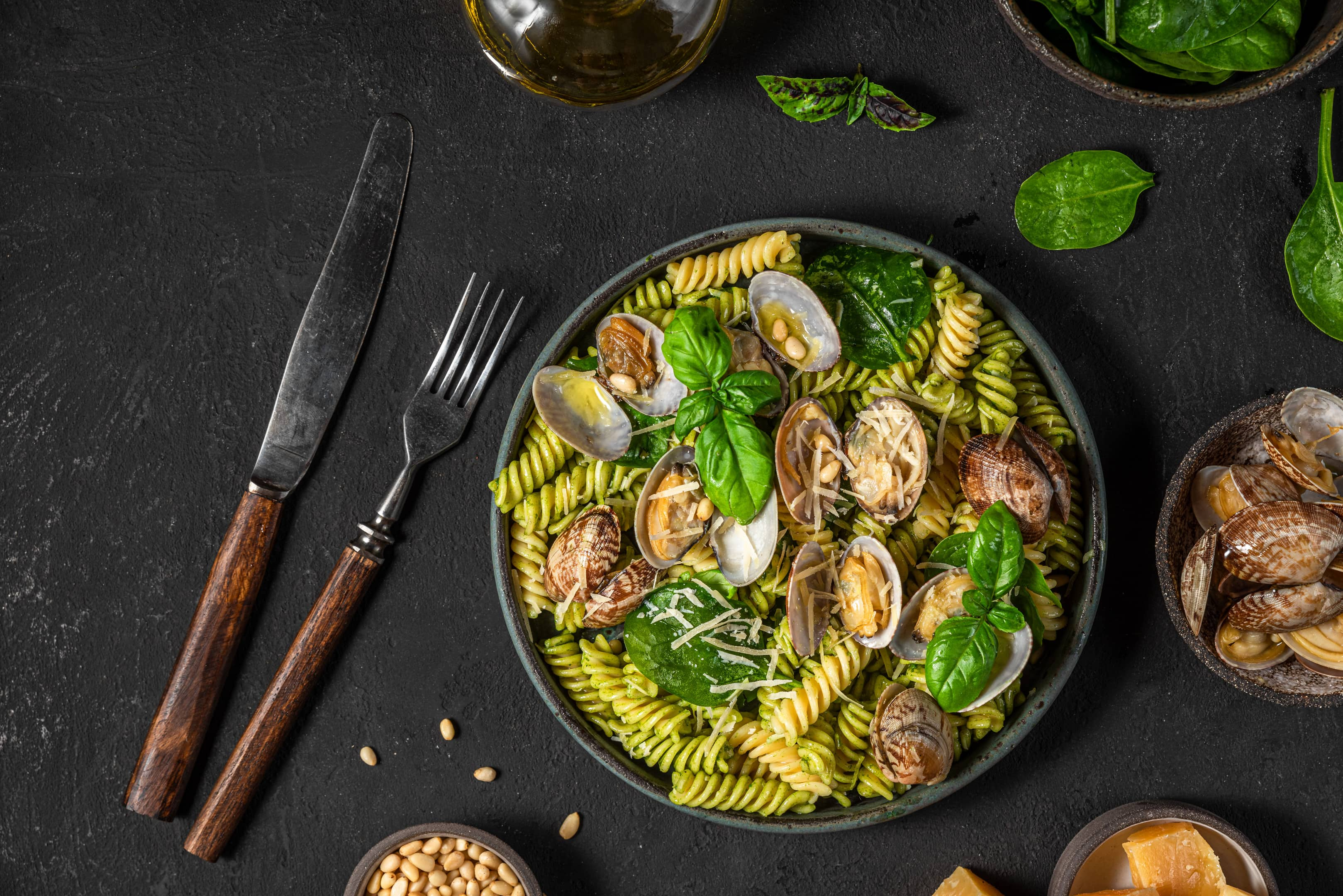 Seafood pasta with vongole clams, spinach parmesan cheese, pine nuts and basil